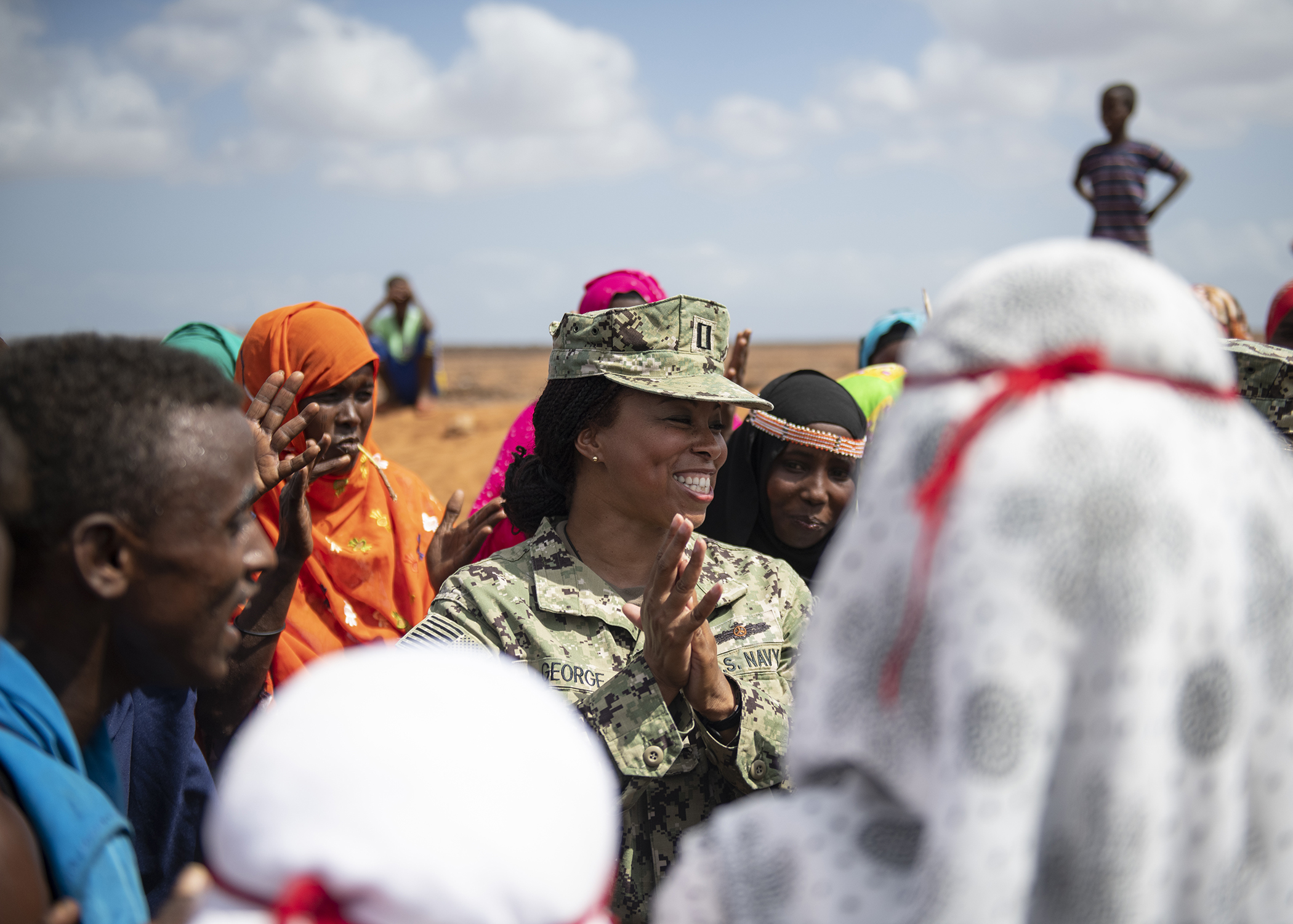 U.S. Navy Lt. Mellany George, an engineering project manager assigned to Combined Joint Task Force-Horn of Africa (CJTF-HOA), laughs as she dances with Djiboutian citizens before the Ali Oune Medical Clinic ribbon cutting ceremony in Ali Oune, Djibouti, Jan. 31, 2019. The clinic, which U.S. Navy Seabees from Naval Mobile Construction Battalion 1, assigned to CJTF-HOA, have been working to complete for five months, is intended to enhance the Ministry of Health for Djibouti's ability to provide basic medical, birth and after care to the Ali Oune village and its more than 1,000 residents and rural neighbors. (U.S. Air Force photo by Tech. Sgt. Shawn Nickel)