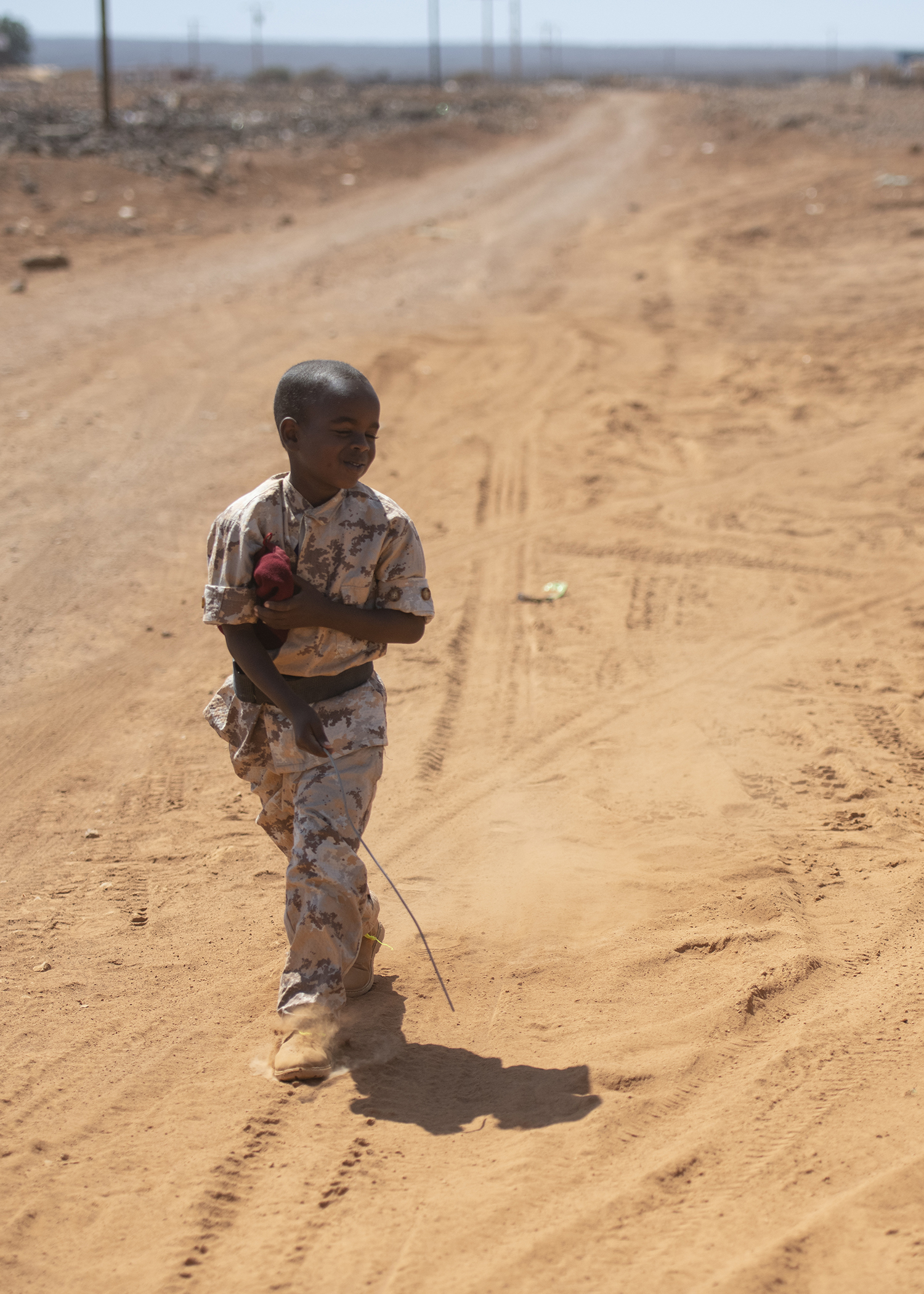 A Djiboutian youth dressed in military-style uniform plays along the road during the Ali Oune Medical Clinic ribbon cutting ceremony in Ali Oune, Djibouti, Jan. 31, 2019. The clinic, which salutes a U.S. Navy Seabee, from Naval Mobile Construction Battalion 1, have been working to complete for five months, is intended to enhance the Ministry of Health for Djibouti's ability to provide basic medical, birth and after care to the Ali Oune village and its more than 1,000 residents and rural neighbors. (U.S. Air Force photo by Tech. Sgt. Shawn Nickel)