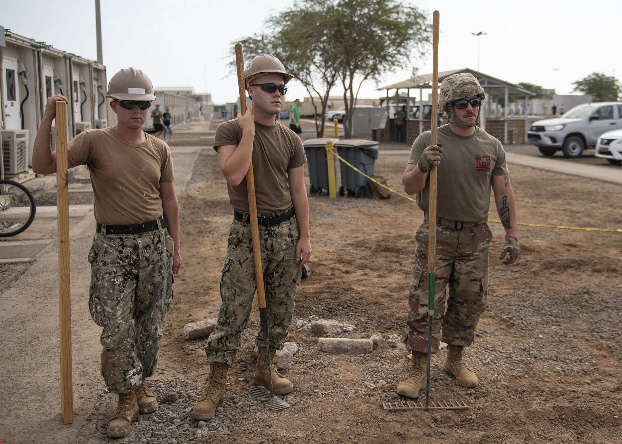 U.S. Navy Seaman Patrick Holt and Petty Officer 3rd Class Joshua McLaughlin, Seabees from Naval Mobile Construction Battalion 1, assigned to Combined Joint Task Force - Horn of Africa (CJTF-HOA), wait for a concrete delivery with U.S. Army Spc. Emmanuel Rodriguez, a carpenter from Second Platoon, 465th Engineer Company, 926th Engineer Battalion, 926th Engineer Brigade, 412th Theater Engineer Command, based in Birmingham, Alabama, assigned to CJTF-HOA, during a construction project Feb. 5, 2019. The two units were working in conjunction as a transition to the 465th EVCC taking over for the Seabees. (U.S. Air Force photo by Tech. Sgt. Shawn Nickel)