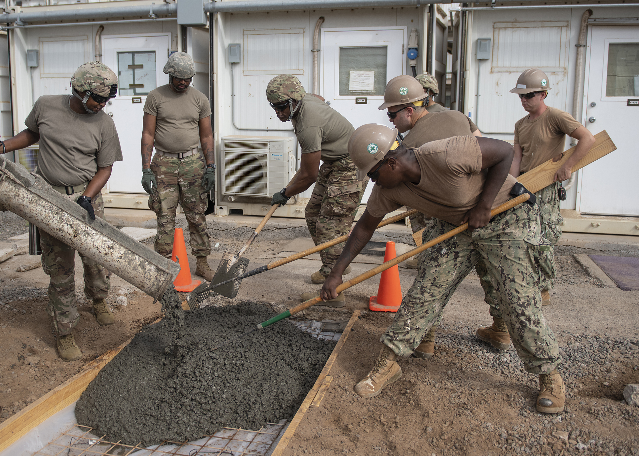 U.S. Navy Seabees from Naval Mobile Construction Battalion 1, assigned to Combined Joint Task Force - Horn of Africa (CJTF-HOA), and U.S. Army Soldiers from Second Platoon, 465th Engineer Company, 926th Engineer Battalion, 926th Engineer Brigade, 412th Theater Engineer Command, based in Birmingham, Alabama, assigned to CJTF-HOA, work side together during a construction project Feb. 5, 2019. The two units were working in conjunction as a transition to the 465th EVCC taking over for the Seabees. (U.S. Air Force photo by Tech. Sgt. Shawn Nickel)