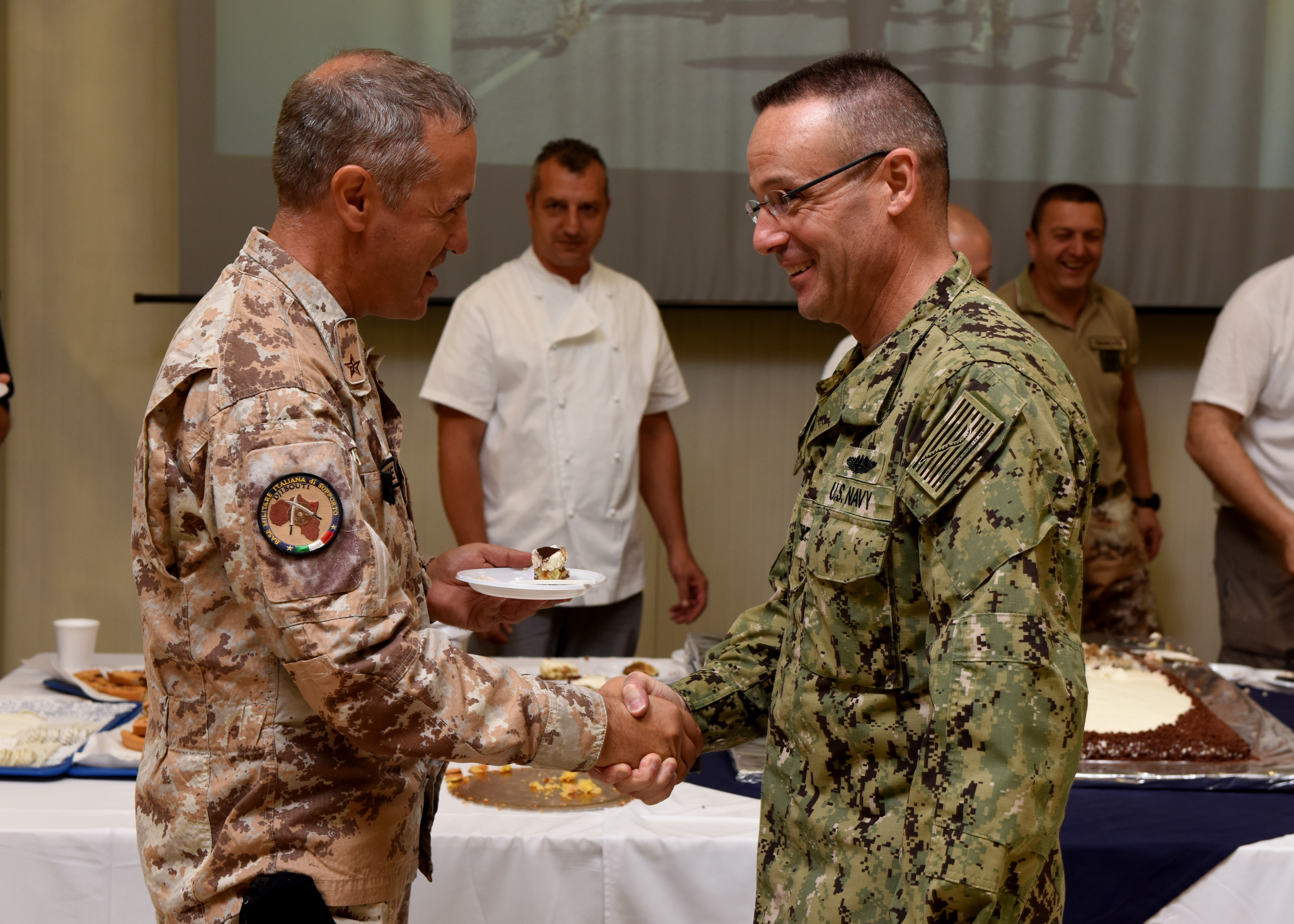 Italian navy Capt. Liborio Palombella, commander of the Italian National Military Support Base, Djibouti, shakes hands with U.S. Navy Capt. Thomas Wall, chief of staff of Combined Joint Task Force-Horn of Africa, during an anniversary ceremony at the Italian National Military Support Base, Feb. 19, 2019. Wall attended the ceremony, which celebrated the Italian base's fifth year in Djibouti, to show support for U.S. partner and coalition forces. (U.S. Air Force photo by Staff Sgt. Franklin R. Ramos)
