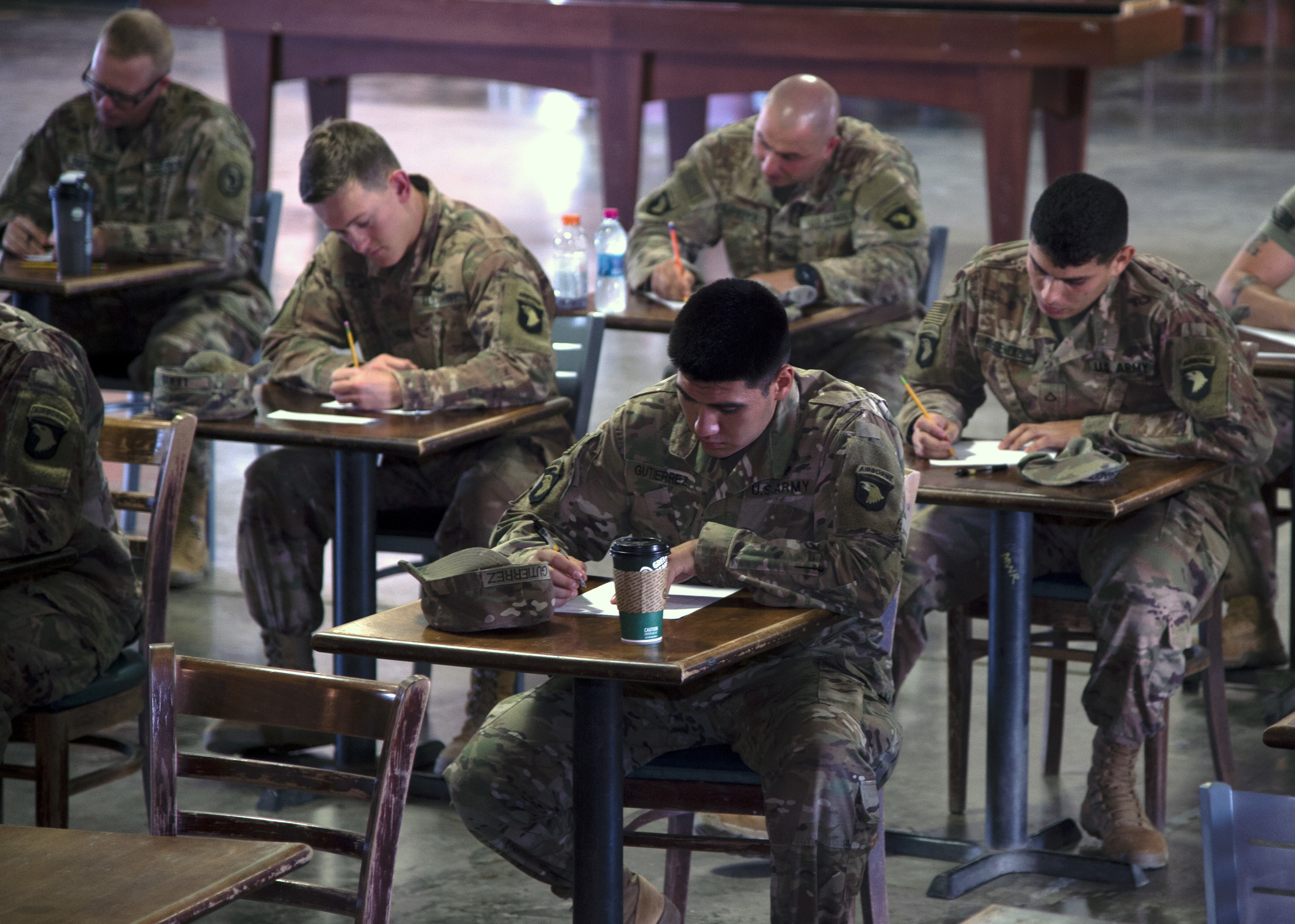 U.S. Army Soldiers assigned to Combined Joint Task Force-Horn of Africa (CJTF-HOA) write during the essay portion of the Joint Warrior Competition (JWC) at Camp Lemonnier, Djibouti, Feb. 26, 2019. The JWC was open to U.S. service members assigned to CJTF-HOA and Camp Lemonnier, and consisted of a 6-mile ruck march with participants carrying bags that weighed no less than 35 pounds, a timed first-aid administration challenge, a timed weapons disassembly and reassembly challenge, a timed essay writing contest, a joint physical training challenge and a combat fitness test. (U.S. Navy photo by Mass Communication Specialist 1st Class Nick Scott)