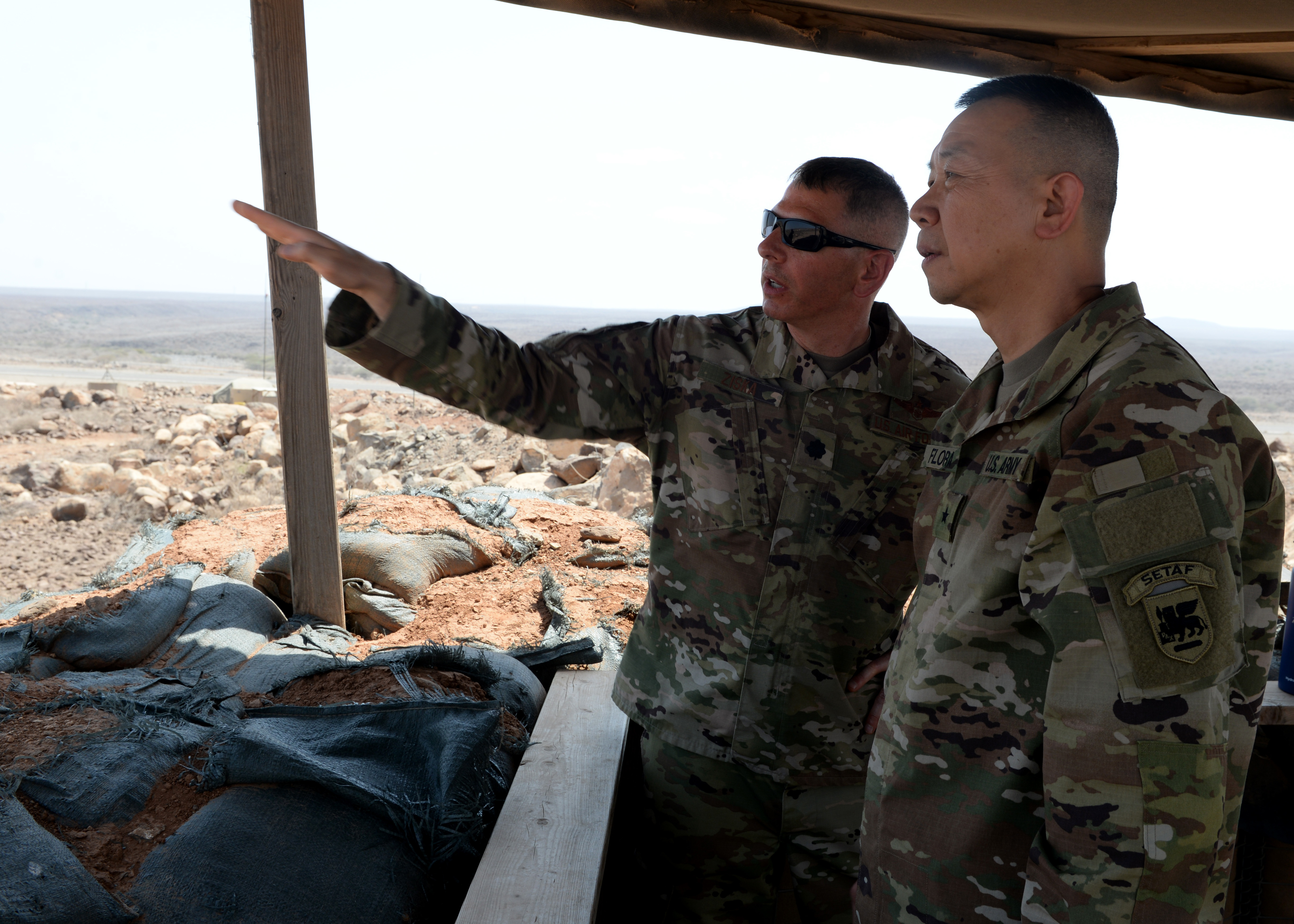 U.S. Army Brig. Gen. Lapthe C. Flora, right, deputy commanding general of U.S. Army Africa (USARAF), listens to U.S. Air Force Lt. Col. Michael Ziska, director of operations for the 870th Air Expeditionary Squadron, supporting Combined Joint Task Force-Horn of Africa (CJTF-HOA), during Flora's visit to a forward operation location in East Africa, March 7, 2019. Flora visited to familiarize himself with the U.S. Army units embedded in CJTF-HOA and to help foster a better partnership between USARAF and CJTF-HOA. (U.S. Air Force photo by Staff Sgt. Franklin R. Ramos)