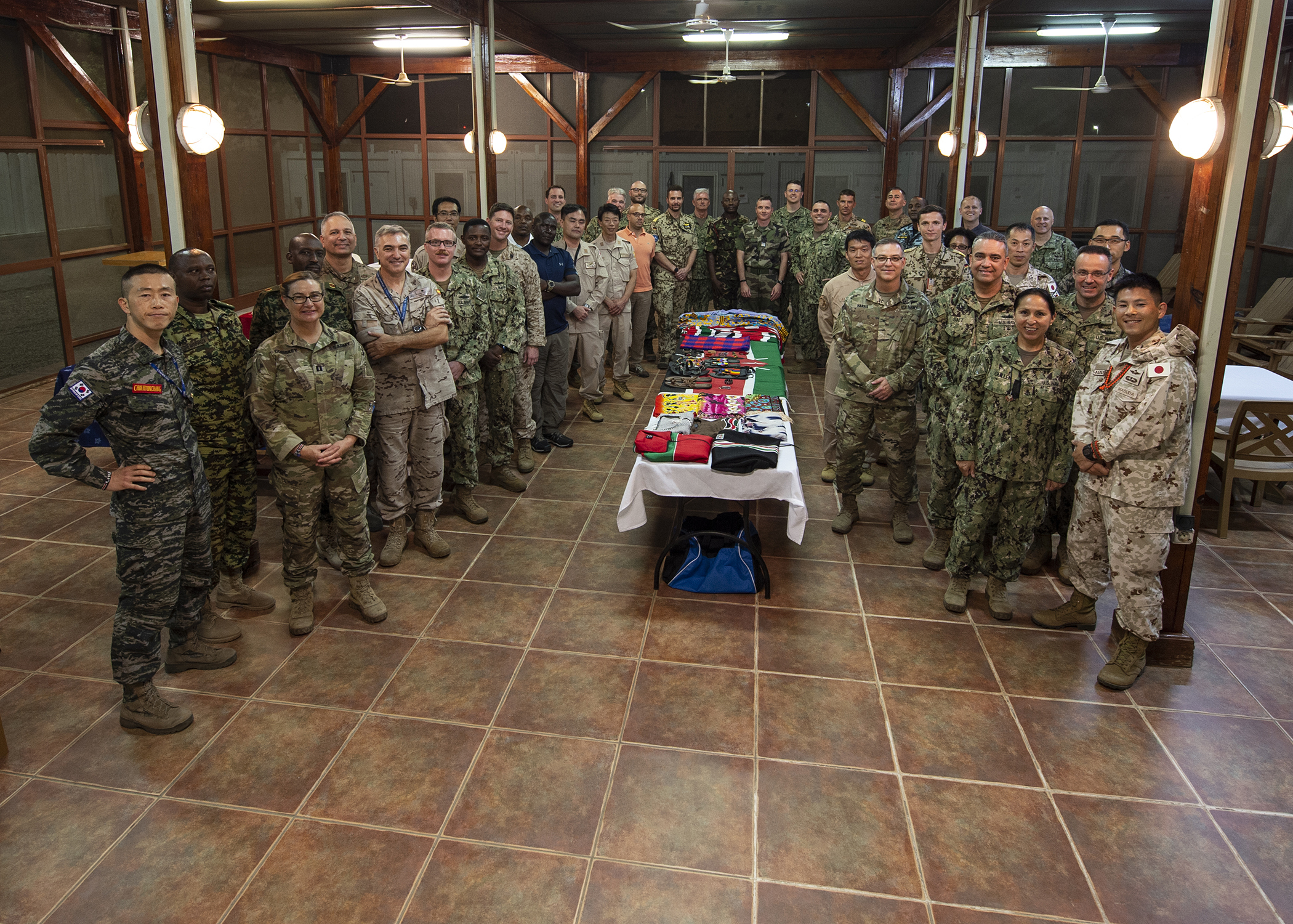 Attendees gather for a group photo at a cultural exchange event led by Kenya Defence Force Lt. Col. Victor Mburu, a foreign liaison officer assigned to Combined Joint Task Force-Horn of Africa (CJTF-HOA), at Camp Lemonnier, Djibouti, March 27, 2019. CJTF-HOA holds monthly exchange events with multinational military partners affiliated with Camp Lemonnier to strengthen alliances and attract new partners in the combined joint military environment. (U.S. Air Force photo by Tech. Sgt. Shawn Nickel)