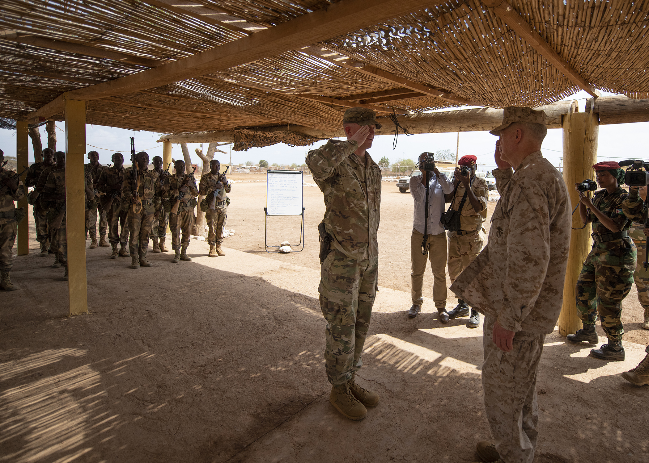 U.S. Marine Corps Gen. Thomas D. Waldhauser, right, commander of U.S. Africa Command, returns the salute of the officer in charge of NCO training for the Rapid Intervention Battalion (RIB), U.S. Army 1st Lt. Travis Holihan, Headquarters Company, 1-26 Infantry Battalion, 2nd Brigade Combat Team, 101st Airborne, assigned to Combined Joint Task Force-Horn of Africa, during a visit with senior Djiboutian officials, including Chief of General Staff of the Djibouti Armed Forces Gen. Zakaria Cheik Ibrahim, at a training base in Djibouti, March 21, 2019. While in Djibouti, Waldhauser observed the ongoing growth and development of the RIB, the Djiboutian army's elite military force, which the U.S. is in the process of training and equipping at the request of the Djiboutian government. (U.S. Air Force photo by Tech. Sgt. Shawn Nickel)
