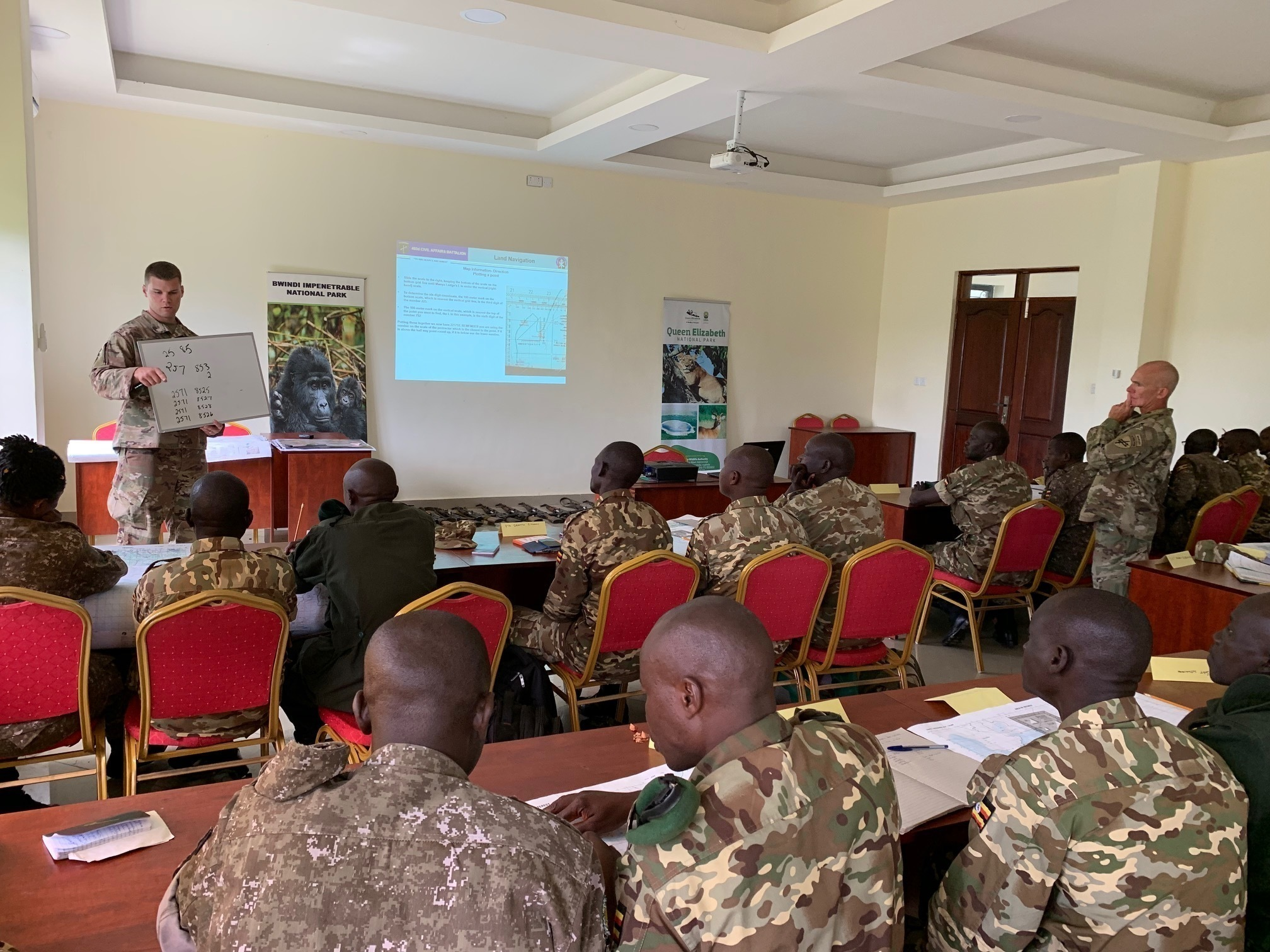 U.S. Army Sgt. Allen Ruffles, a 403rd Civil Affairs Battalion soldier assigned to Combined Joint Task Force-Horn of Africa (CJTF-HOA), speaks to African coalition partners during a navigation class in Kampala, Uganda, May 20, 2019. Personnel from the civil affairs battalion travelled to Uganda to take part in a subject matter expert exchange with coalition forces as part of a Uganda Wildlife Authority counter-illicit trafficking course. (Courtesy photo)