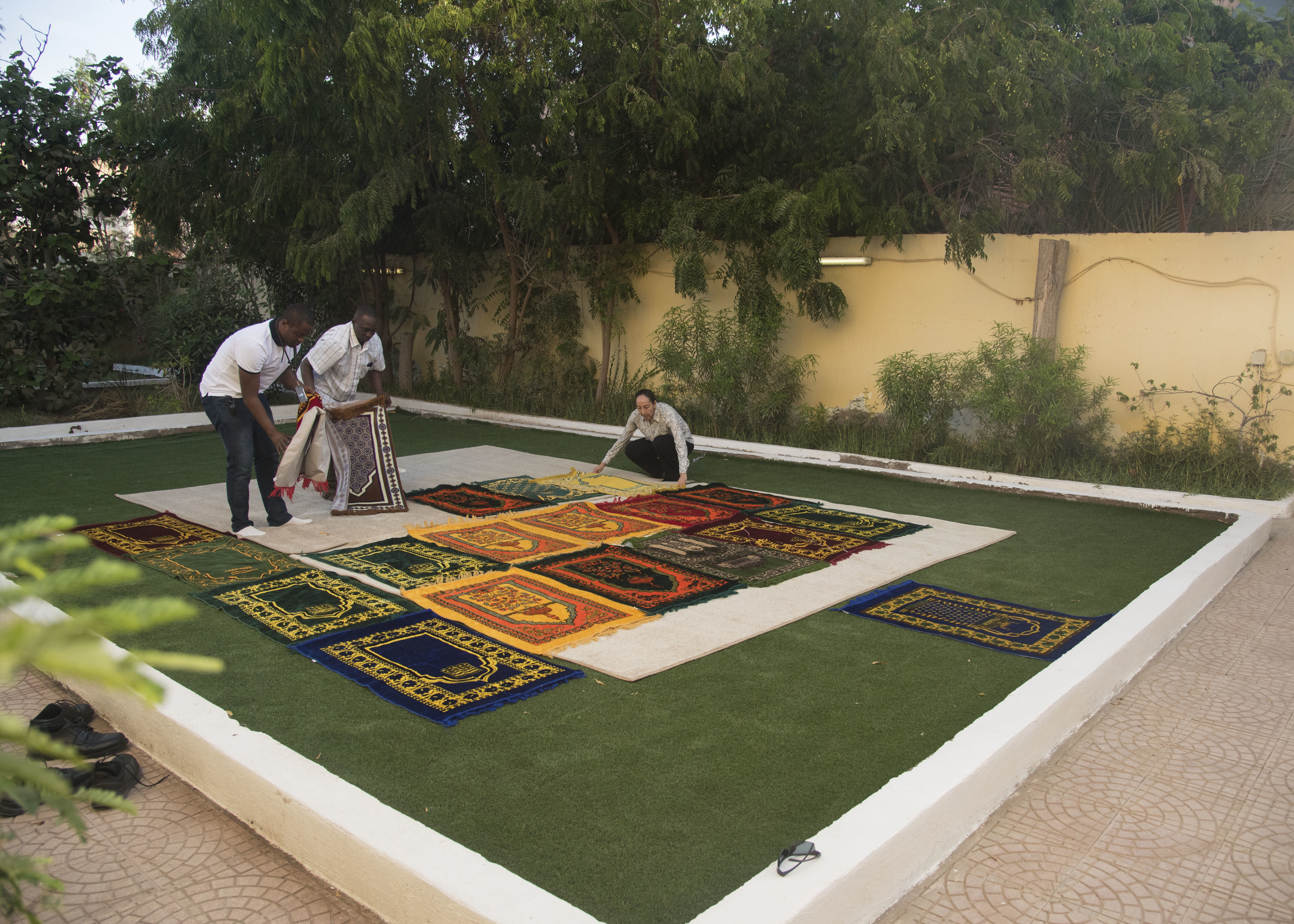 People prepare prayer rugs for an Iftar celebration at the home of U.S. Embassy Djibouti's senior defense attaché in Djibouti, May 12, 2019. The Iftar is a fast-breaking meal Muslims eat after sunset during Ramadan, the ninth month of the Islamic year observed with daily fasting from dawn to sunset. (U.S. Air Force photo by Staff Sgt. Kirsten Brandes)