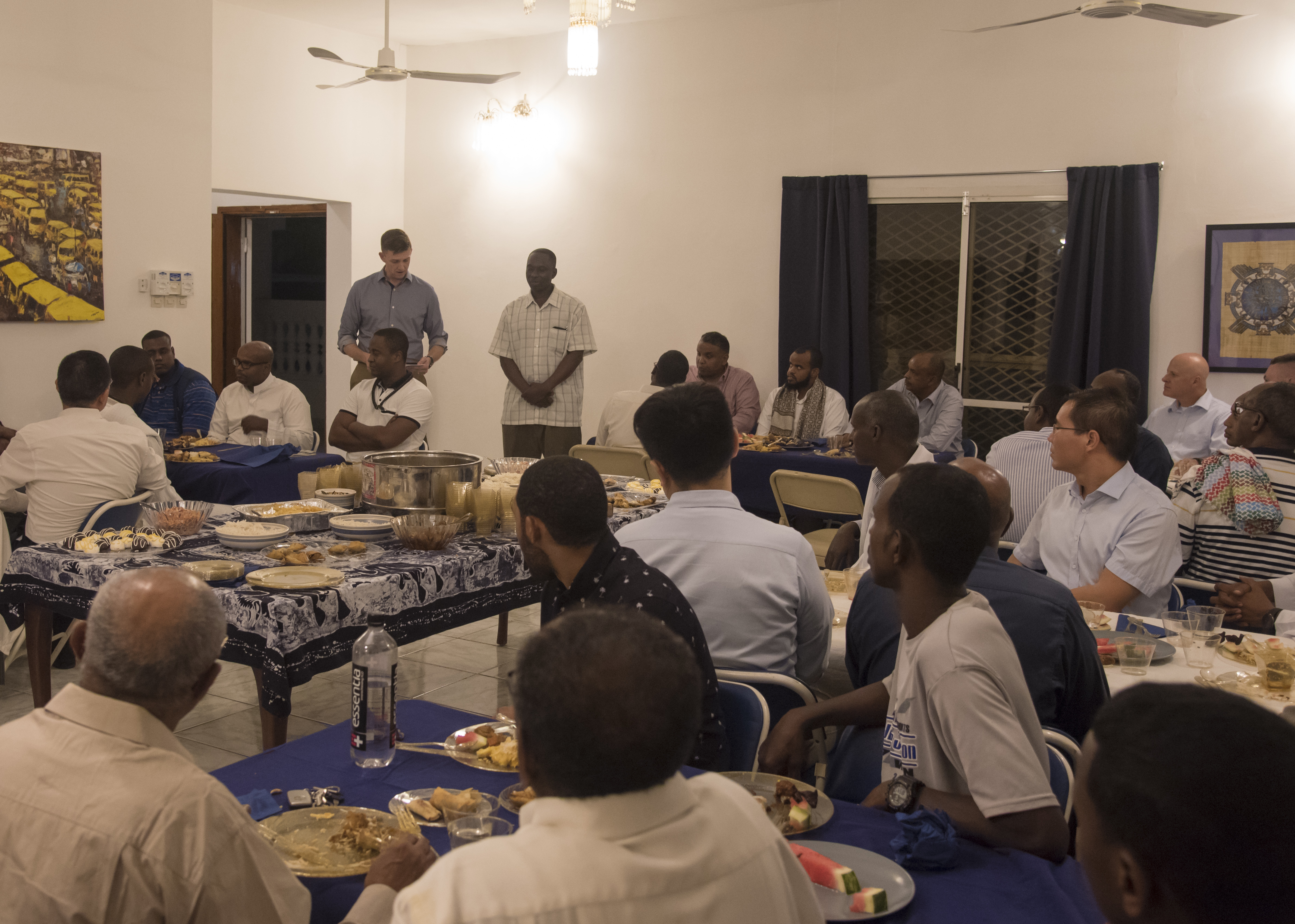 U.S. Navy Cmdr. Sean Hays, U.S. Embassy Djibouti senior defense official and defense attaché, introduces U.S. Army Capt. Ayub Laari, a chaplain assigned to the 39th Transportation Battalion, Kleber Kaserne, Germany, during an Iftar celebration, May 12, 2019. The Iftar is a fast-breaking meal Muslims eat after sunset during Ramadan, the ninth month of the Islamic year observed with daily fasting from dawn to sunset. Laari served as the event's Imam, a worship leader in the Islamic faith. (U.S. Air Force photo by Staff Sgt. Kirsten Brandes)