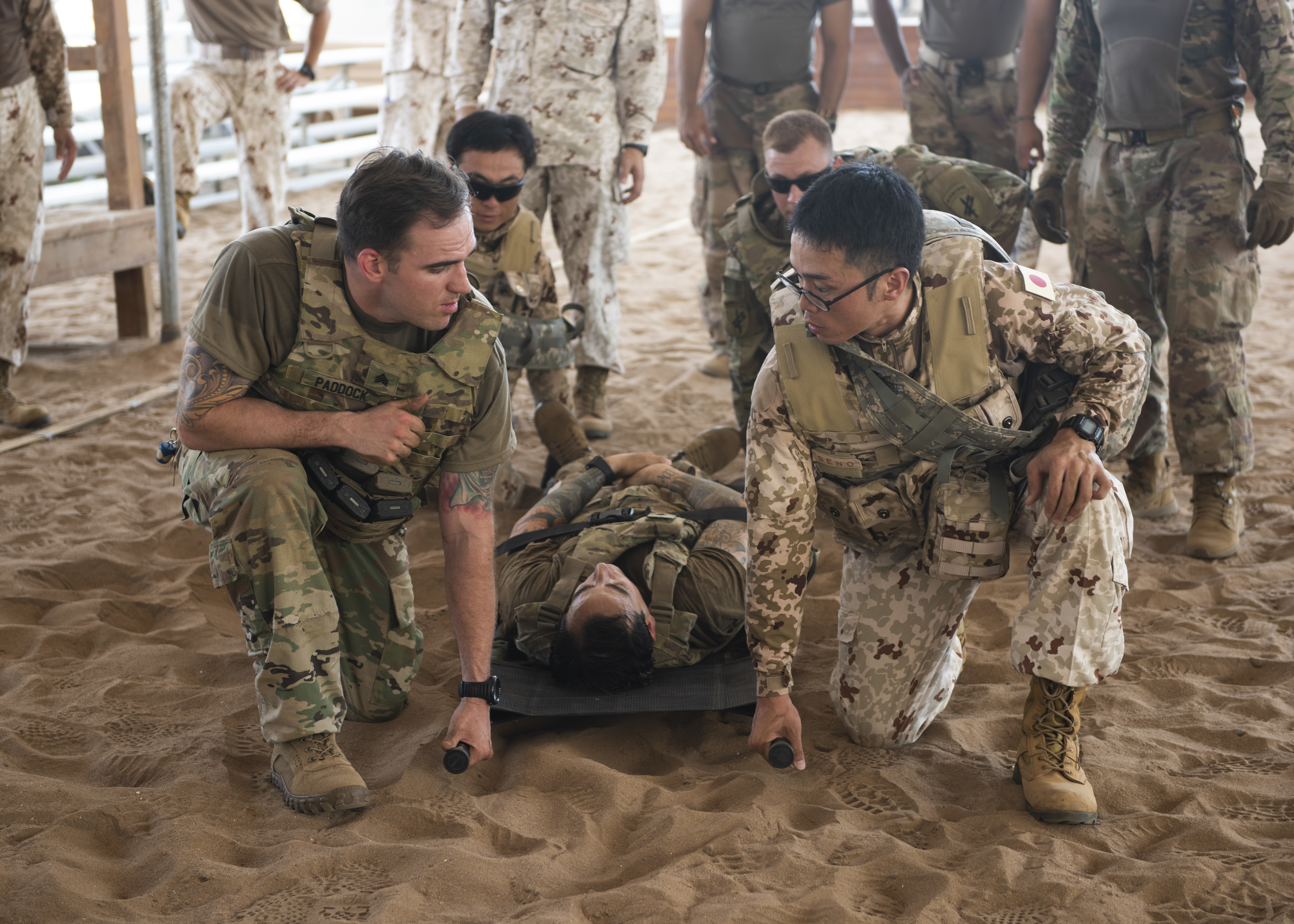 U.S. Army Soldiers assigned to Combined Joint Task Force-Horn of Africa and Japanese Ground Self-Defense Force soldiers prepare to carry a victim during a tactical combat casualty care (TCCC) medical exchange at Camp Lemonnier, Djibouti, June 3, 2019. TCCC provided partner nation soldiers an opportunity to share different methods on how to conduct life-saving medical care on a battlefield. (U.S. Air Force photo by Staff Sgt. Franklin R. Ramos)