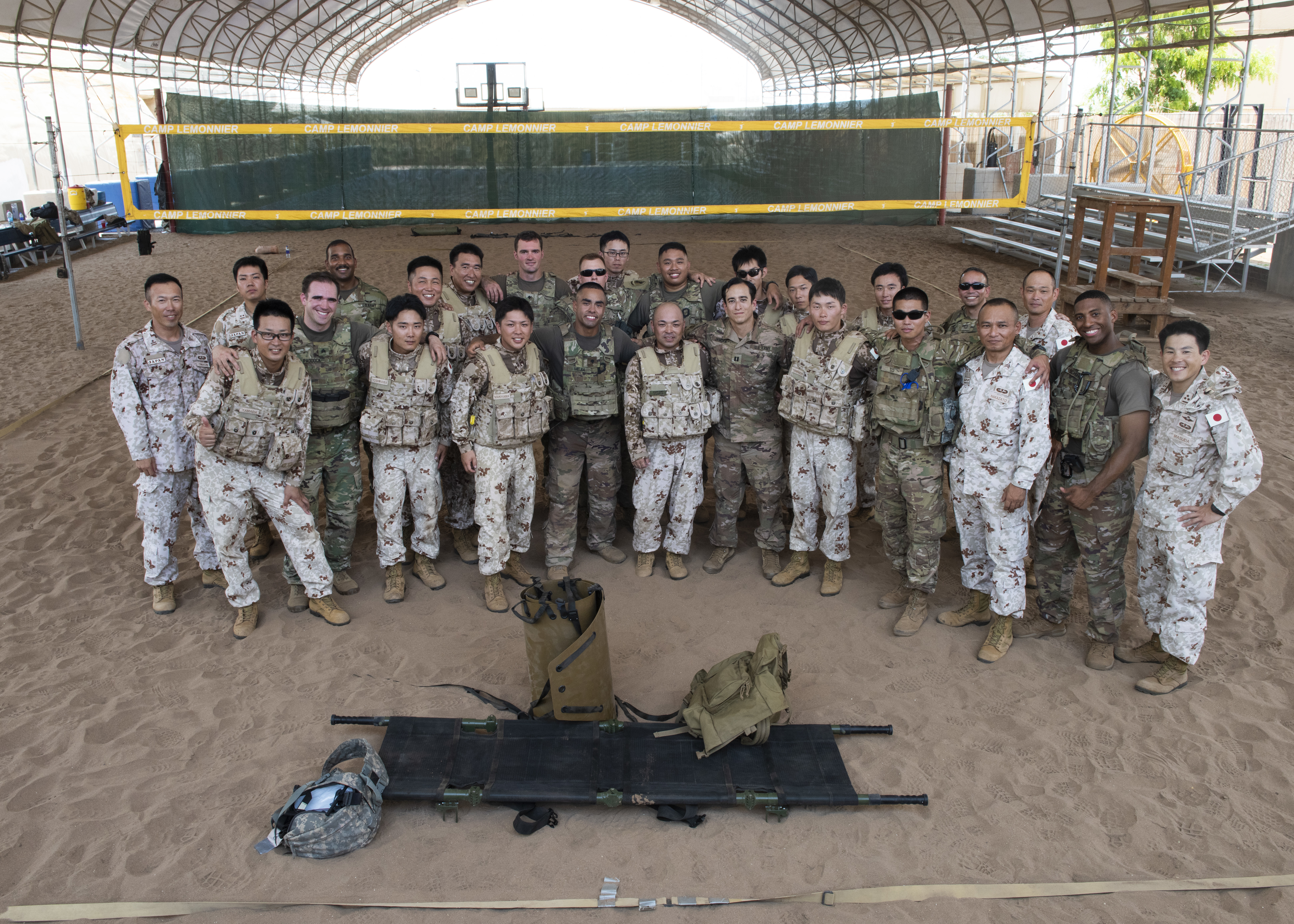 U.S. Army Soldiers assigned to Combined Joint Task Force-Horn of Africa and Japanese Ground Self-Defense Force soldiers pose for a group photo during a tactical combat casualty care course at Camp Lemonnier, Djibouti, June 3, 2019. The course was part of a two-day subject matter expert medical exchange that focused on first-aid methodologies between the two partner nations in Djibouti. (U.S. Air Force photo by Staff Sgt. Franklin R. Ramos)