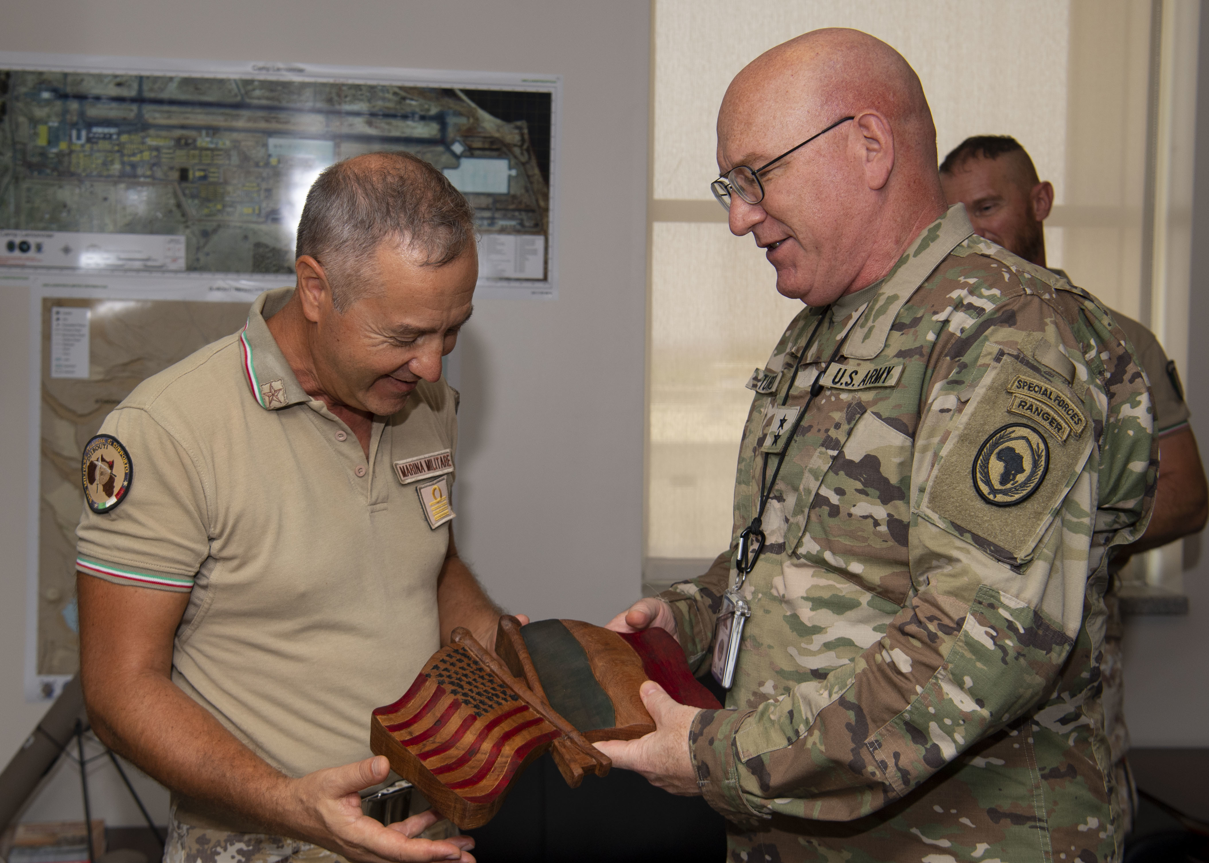 U.S. Army Maj. Gen. Michael D. Turello, commanding general, Combined Joint Task Force-Horn of Africa (CJTF-HOA), right, presents Italian navy Capt. Liborio Palombella, deputy commander, Italian Navy Training Center, left, with a gift after his visit to Camp Lemonnier, Djibouti, July 15, 2019. Palombella visited Camp Lemonnier to learn about the CJTF-HOA mission and its contributions to East Africa. (U.S. Air Force photo by Staff Sgt. J.D. Strong II)