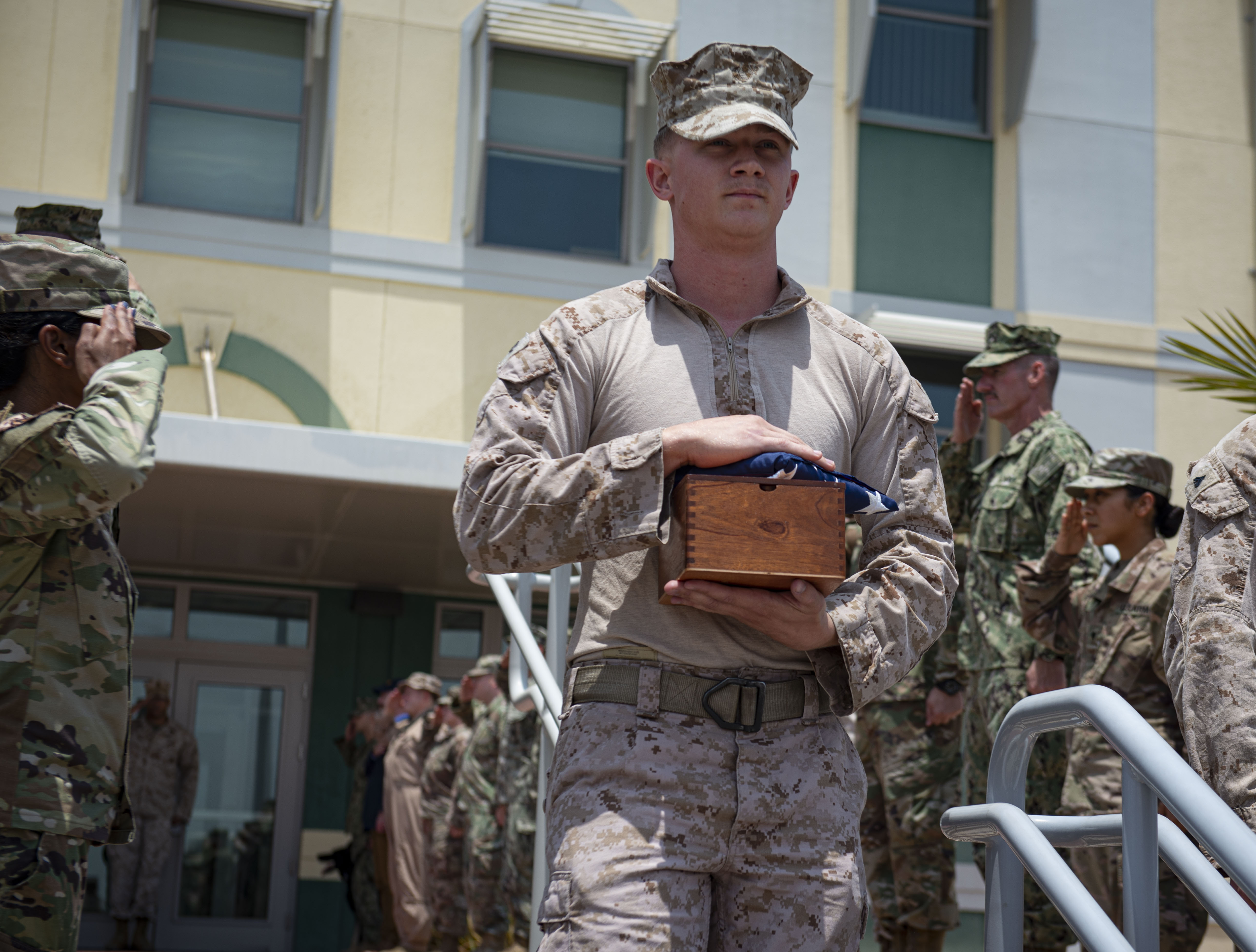 U.S. Marine Corporal Cameron Woodside, military working dog handler, assigned to Combined Joint Task Force-Horn of Africa (CJTF-HOA), holds the remains of Aarno, military working dog, during a dignified transfer at Camp Lemonnier, Djibouti (CLDJ), Sept. 19, 2019. Aarno passed away of natural causes while assigned to CJTF-HOA. (U.S. Air Force photo by Senior Airman Gabrielle Spalding)