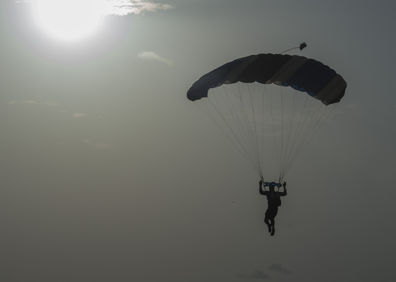 A French Forces soldier prepares to land on a drop zone after a High Altitude, Low Opening (HALO) jump outside Djibouti City, Djibouti, Sept. 29, 2019.  American service members and coalition partners jumped together to celebrate the Feast Day of Archangel Michael, the patron saint of paratroopers. (U.S. Air Force Photo by Senior Airman Codie Trimble) (U.S. Air Force Photo by Senior Airman Codie Trimble)