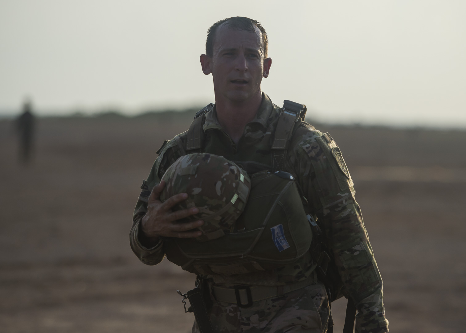 U.S. Army Lt. Col. Cecil Piazza, commander, 411th Civil Affairs Battalion, assigned to Combined Joint Task Force-Horn of Africa, walks away from the drop zone after a static-line jump with American and coalition partners, outside Djibouti City, Djibouti, Sept. 29, 2019. American service members and coalition partners jumped together to celebrate the Feast Day of Archangel Michael, the patron saint of paratroopers. (U.S. Air Force Photo by Senior Airman Codie Trimble)