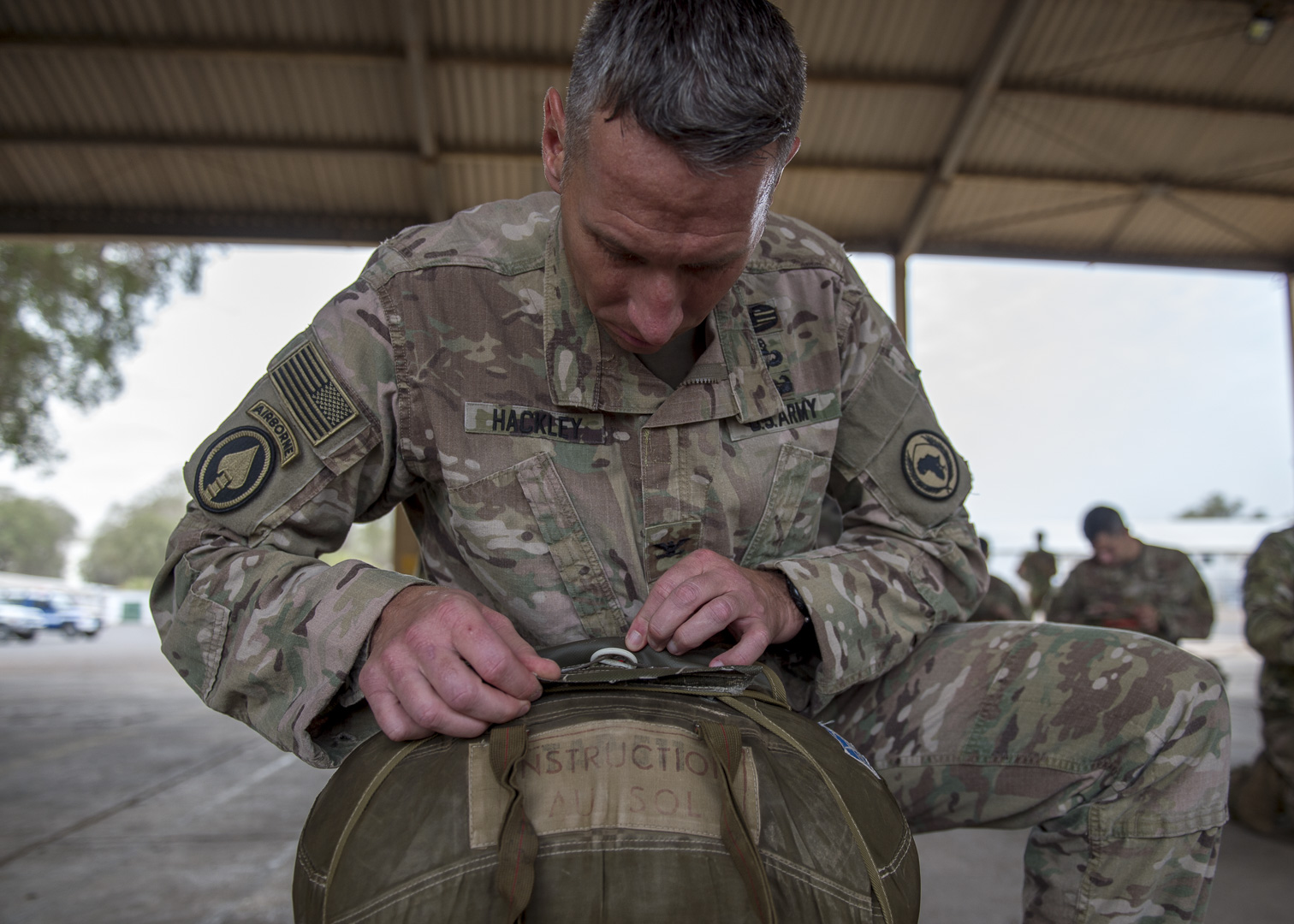 U.S. Army Col. Chad Hackley, director of intelligence, assigned to the Combined Joint Task Force-Horn of Africa, inspects his parachute during a training event with French Forces Djibouti, at Djibouti Air Base, Djibouti, Sept. 26, 2019. American service members and coalition partners jumped together to celebrate the Feast Day of Archangel Michael, the patron saint of paratroopers.(U.S. Air Force Photo by Senior Airman Codie Trimble)