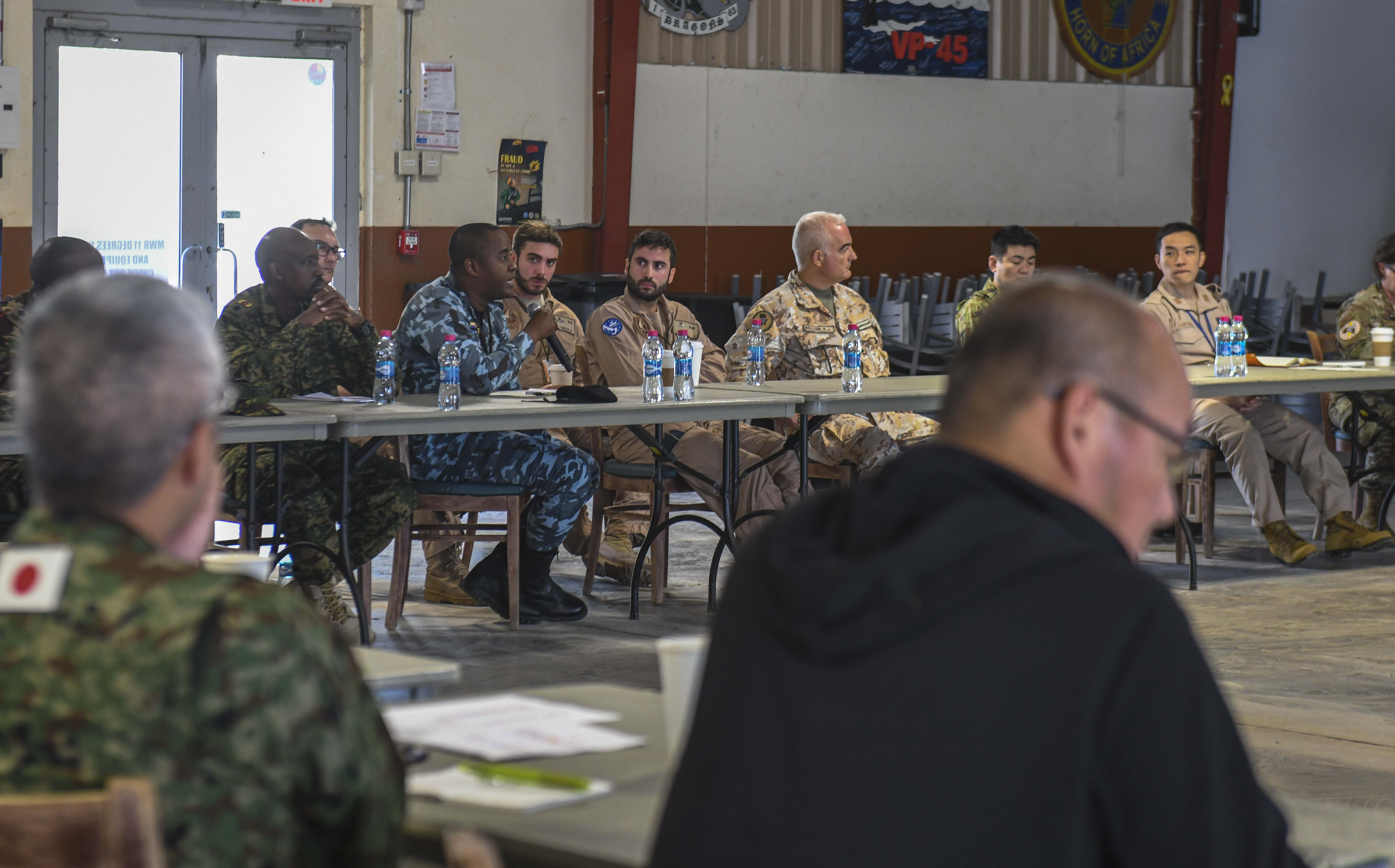 Multinational service members and representatives take part in a tabletop discussion during an annual noncombatant evacuation operation (NEO) exercise held at Camp Lemonnier, Djibouti, Oct. 4, 2019. Service members assigned to Combined Joint Task Force-Horn of Africa (CJTF-HOA) worked together with the Japan Self-Defense Force (JSDF) to share capabilities during the multi-day event, which was held from Oct. 1-4. (U.S. Air Force photo by Senior Airman Gabrielle Spalding)
