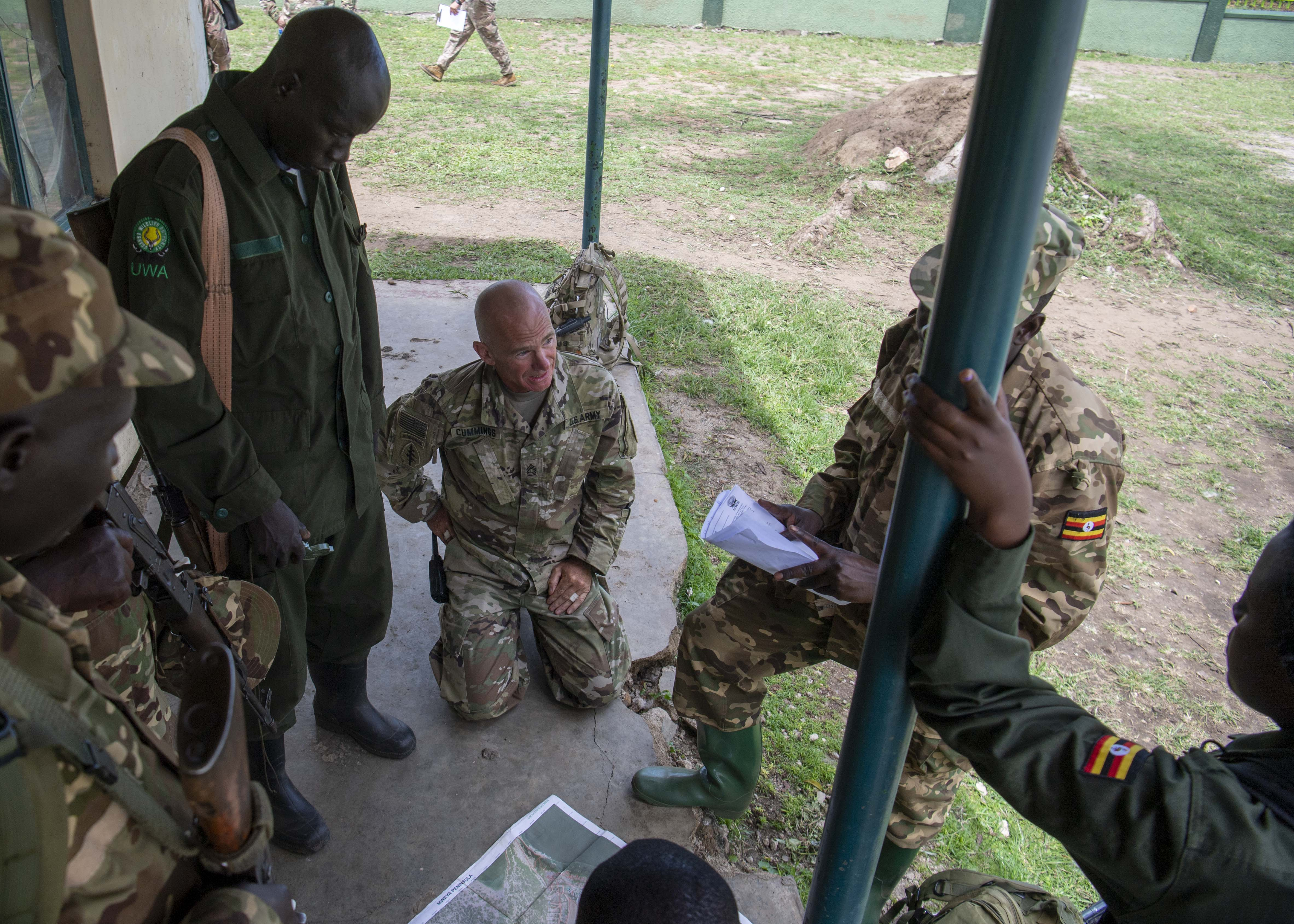 U.S. Army Master Sgt. James Cummings, instructor, 403rd Civil Affairs Battalion assigned to Combined Joint Task Force-Horn of Africa writes a team evaluation during a Counter Illicit Trafficking Junior Leadership Course examination at Queen Elizabeth Park, Uganda, Oct. 10, 2019. Cummings was one of six instructors who taught Uganda Wildlife Authority (UWA) Rangers how to conduct land navigation, conduct small unit tactics, respond to wildlife crimes, ethics and medically treat a casualty. (U.S. Air Force photo by Staff Sgt. J.D. Strong II)