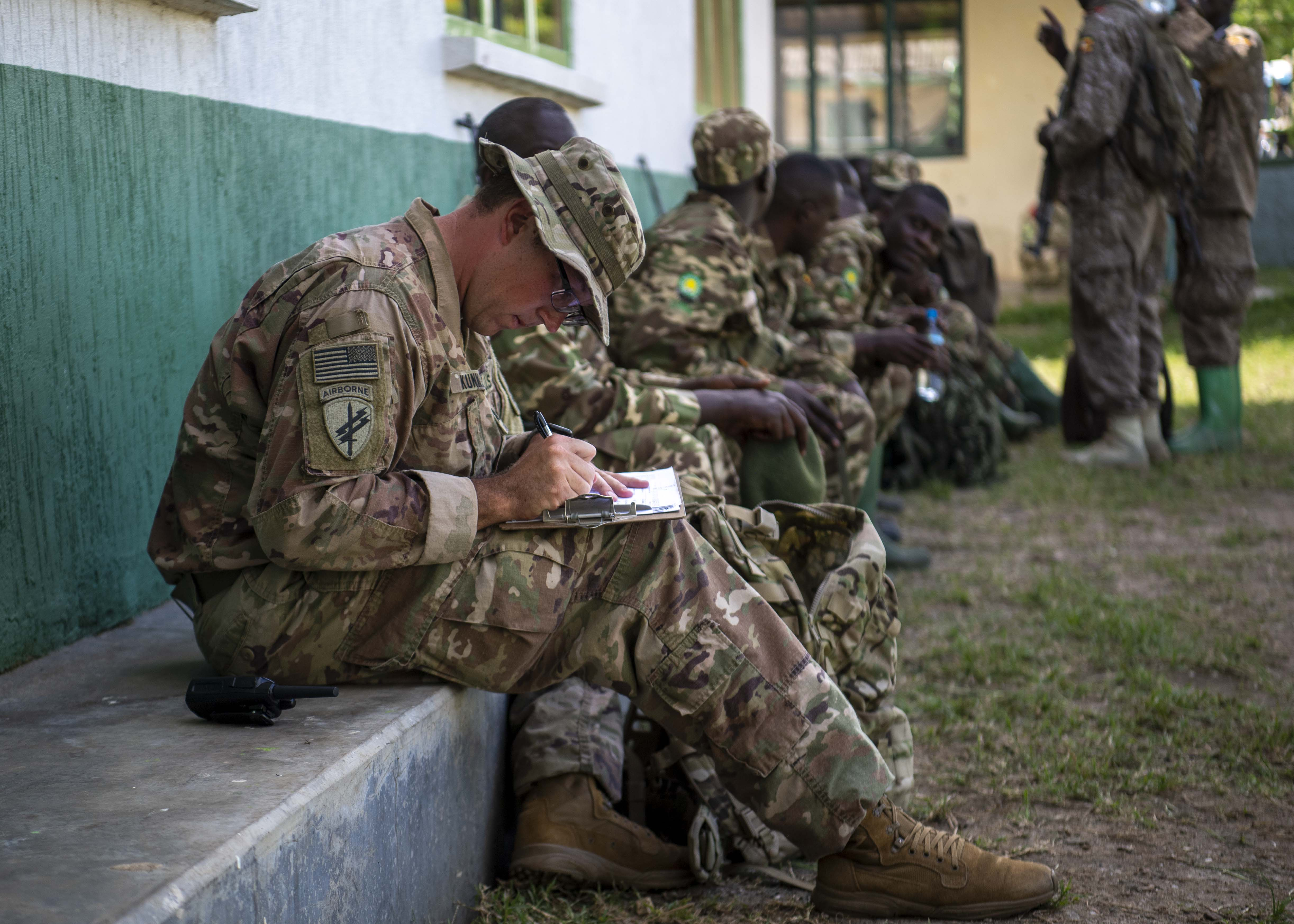 U.S. Army Sgt. Jason Kunkle, instructor, 403rd Civil Affairs Battalion assigned to Combined Joint Task Force-Horn of Africa writes a team evaluation during a Counter Illicit Trafficking Junior Leadership Course examination at Queen Elizabeth Park, Uganda, Oct. 10, 2019. Kunkle was one of six instructors who taught Uganda Wildlife Authority (UWA) Rangers how to conduct land navigation, conduct small unit tactics, respond to wildlife crimes, ethics and medically treat a casualty. (U.S. Air Force photo by Staff Sgt. J.D. Strong II)
