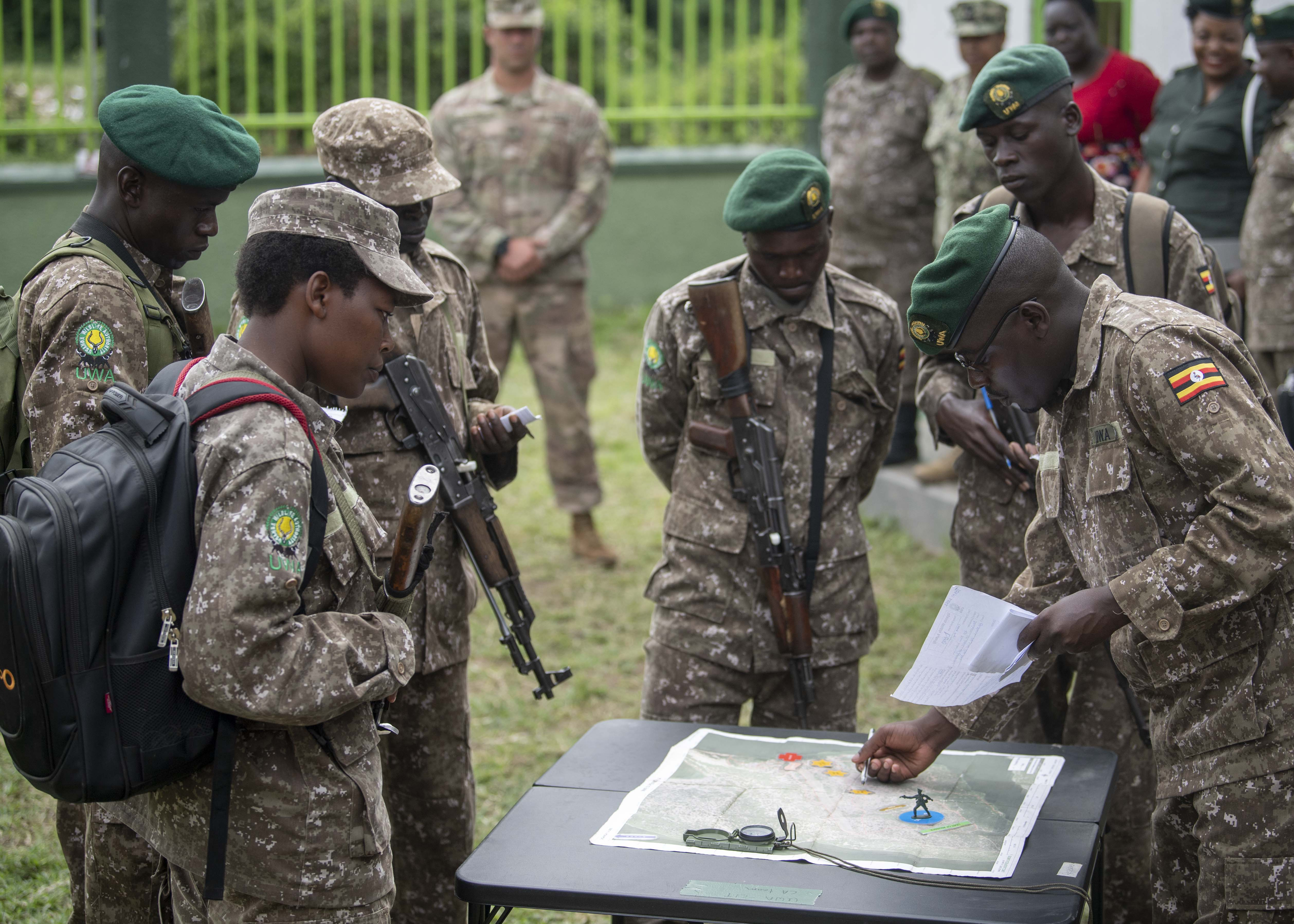 Uganda Wildlife Authority (UWA) Rangers discuss land navigation during a Counter Illicit Trafficking Junior Leadership Course graduation demonstration at Queen Elizabeth Park, Uganda, Oct. 10, 2019. Twenty-five UWA Rangers graduated the course. (U.S. Air Force photo by Staff Sgt. J.D. Strong II)