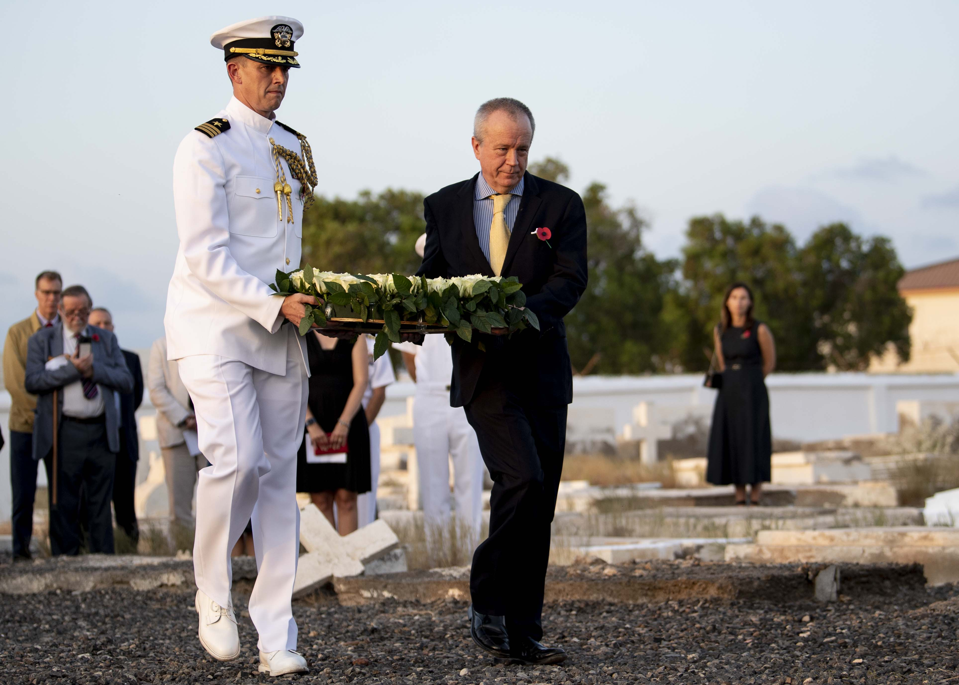 Amb. Larry André Jr., U.S. Ambassador to the Republic of Djibouti and U.S. Navy Cdr. Sean Hayes, defense attaché, U.S. Embassy Djibouti, walk to place a wreath at a memorial during a Remembrance Day service in Djibouti City, Djibouti, Nov. 13, 2019. Traditionally observed on November 11, Remembrance Day commemorates the day hostilities stopped on the western front during World War I. (U.S. Air Force photo by Staff Sgt. J.D. Strong II)