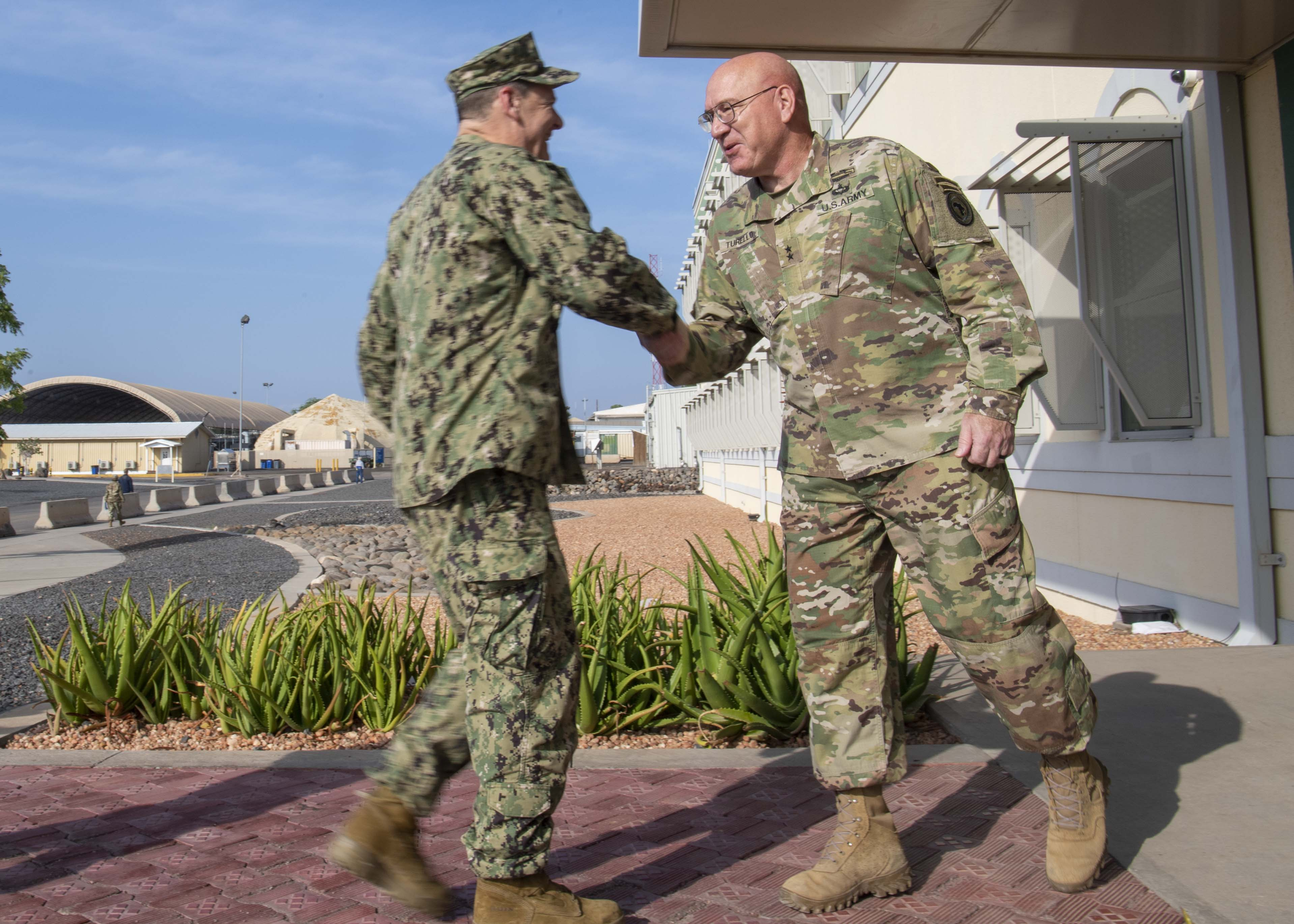 U.S. Army Maj. Gen. Michael Turello, commanding general, Combined Joint Task Force-Horn of Africa (CJTF-HOA), (right), greets U.S. Navy Vice Adm. Luke McCollum, commander, Navy Reserve Force, chief, Navy Reserve at Camp Lemonnier, Djibouti, Nov. 29, 2019. McCollum visited Camp Lemonnier to meet with deployed Navy Reserve sailors and other service members. (U.S. Air Force photo by Staff Sgt. J.D. Strong II)