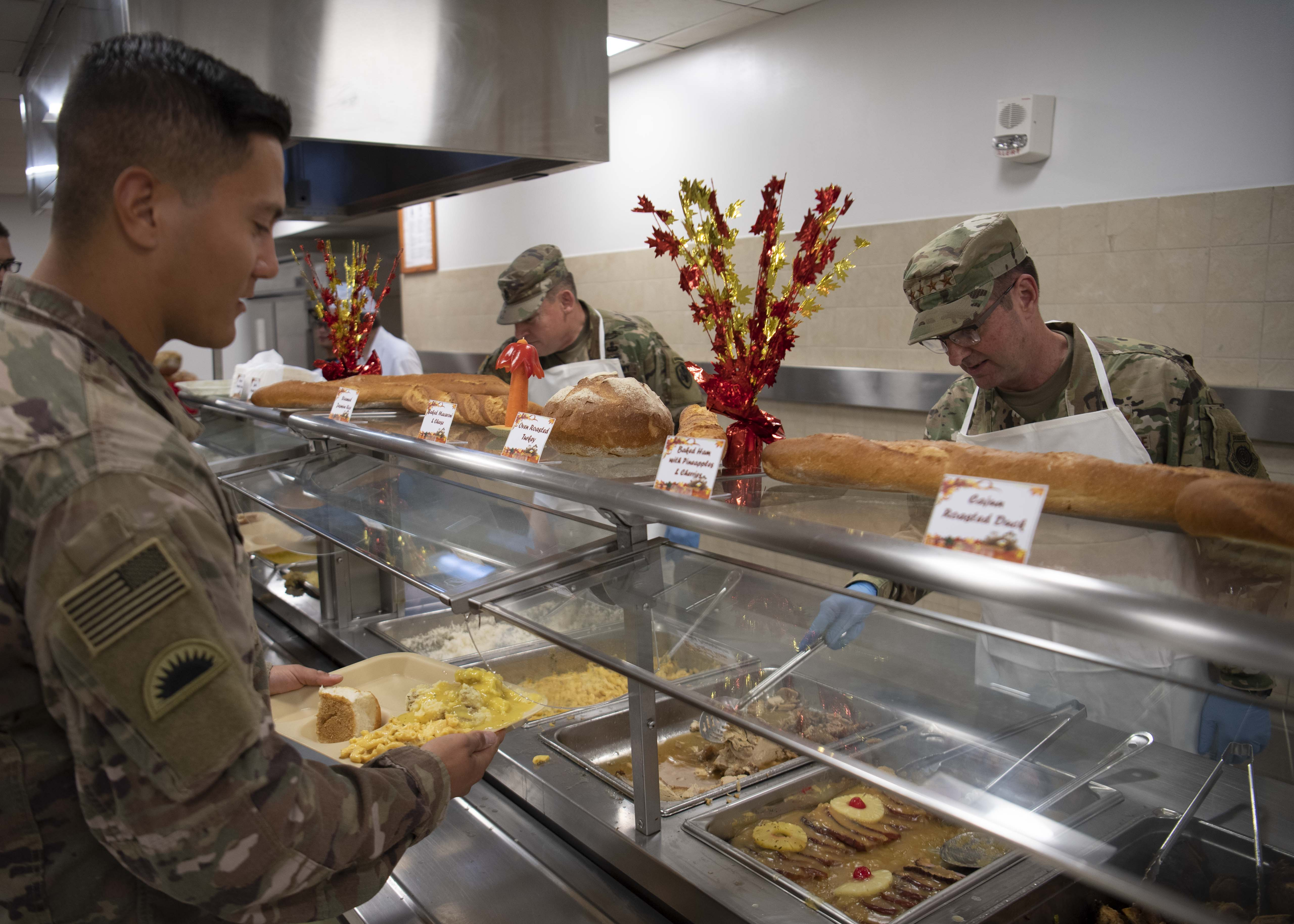 U.S. Air Force Gen. Joseph Lengyel, chief, National Guard Bureau, (right), serves Thanksgiving dinner to a U.S. soldier at Camp Lemonnier, Djibouti, Nov. 28, 2019. Lengyel visited Camp Lemonnier to meet with deployed National Guardsmen and other service members. (U.S. Air Force photo by Staff Sgt. J.D. Strong II)