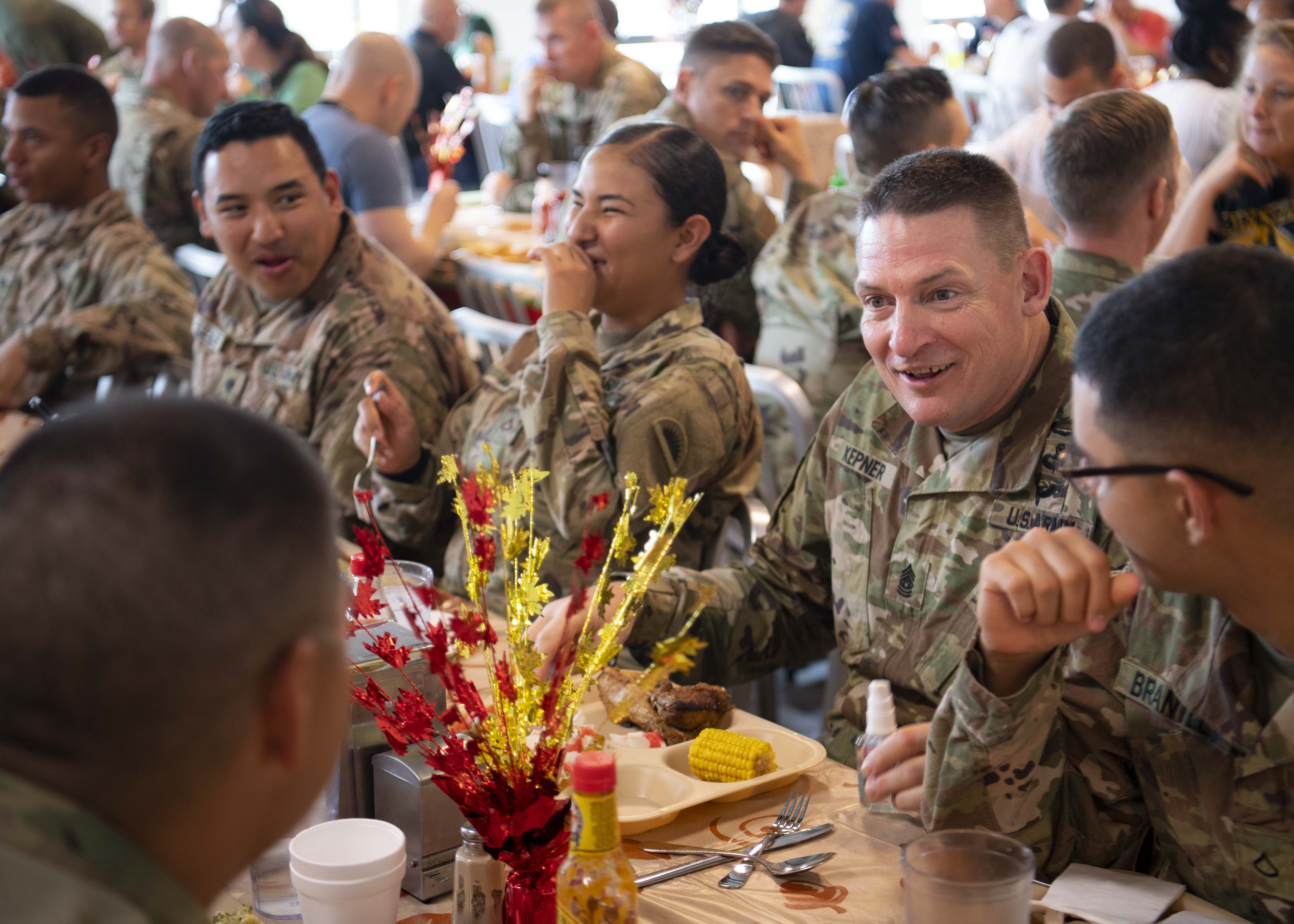 U.S. Army Command Sgt. Maj. Christopher Kepner, senior enlisted advisor to the Chief, National Guard Bureau, (center right), eats Thanksgiving dinner with U.S. service members at Camp Lemonnier, Djibouti, Nov. 28, 2019. Kepner visited Camp Lemonnier to meet with deployed National Guardsmen and other service members. (U.S. Air Force photo by Staff Sgt. J.D. Strong II)