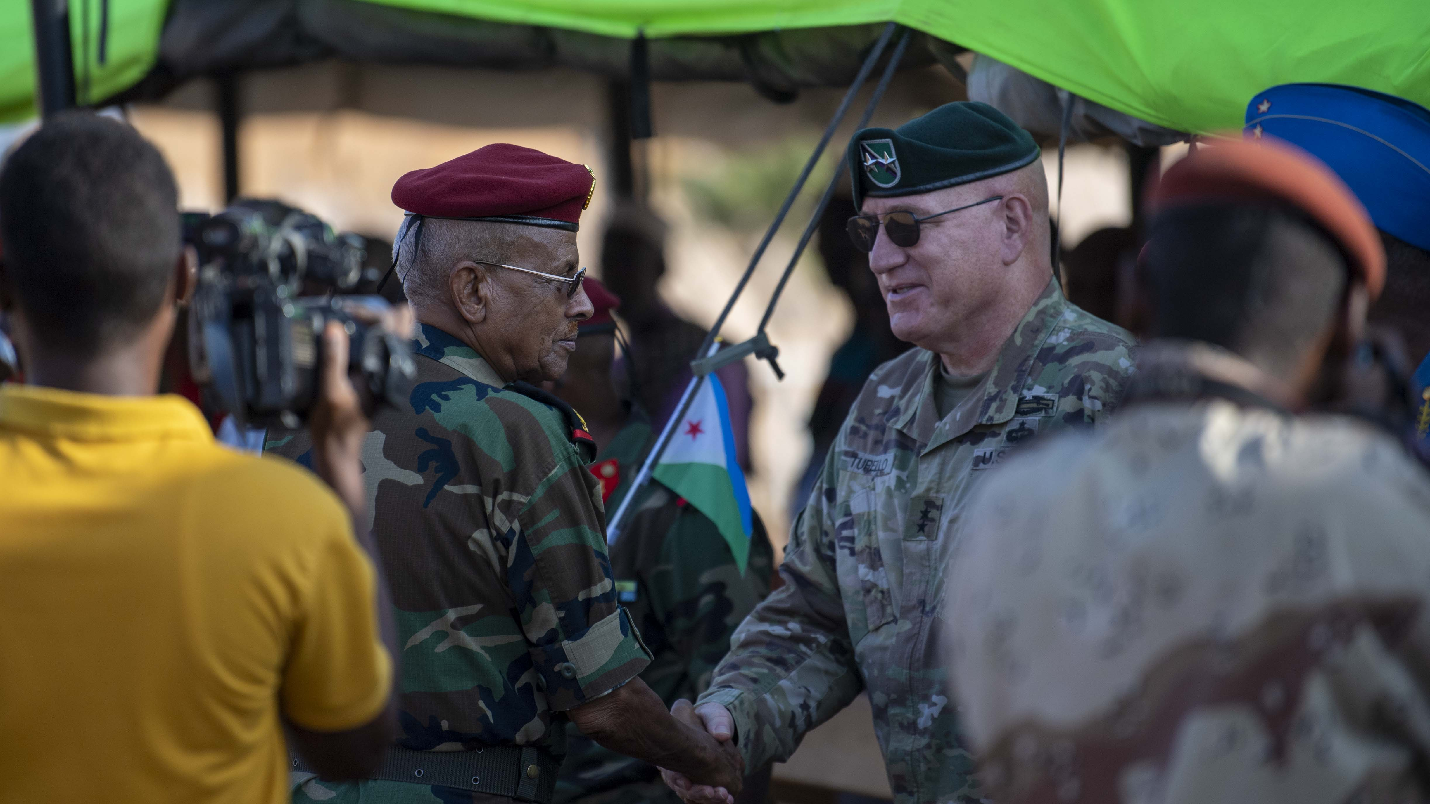U.S. Army Maj. Gen. Michael D. Turello, commanding general of Combined Joint Task Force-Horn of Africa (CJTF-HOA) (right) shakes hands with Djiboutian Lt. Gen. Zakaria Cheikh Ibrahim, chief of staff of the Djibouti Armed Forces, during the Rapid Intervention Battalion (RIB) change of command, in Djibouti, Oct. 31, 2019. Djiboutian Maj. Mohamed Assowen assumed command of the RIB from Djiboutian Capt. Omar Ali Hassan. (U.S. Air Force photo by Staff Sgt. J.D. Strong II)