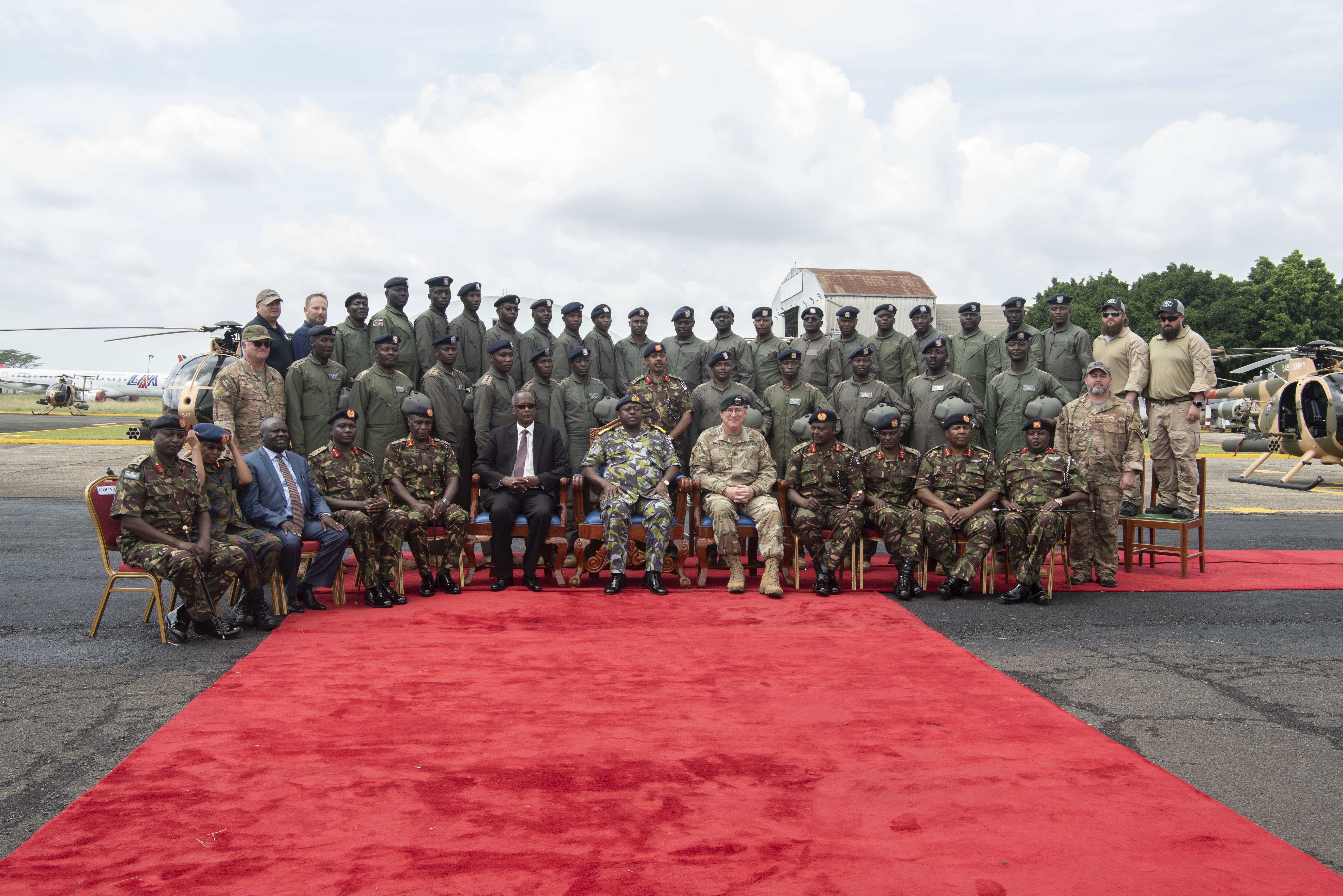 U.S. Army Maj. Gen. Michael D. Turello, commanding general of Combined Joint Task Force-Horn of Africa, center right, and Gen. Samson Mwathethe, chief of Kenyan Defense Forces (KDF), center left, take a group photo with members from the KDF during a Helicopter Handover Ceremony at Embakasi Barracks, Kenya, Jan. 23, 2020. During the ceremony, six MD-530F Cayuse Warrior helicopters were delivered to the KDF in a symbolic handover. Six more MD-530F helicopters will be delivered to the KDF in the near future. (U.S. Air Force photo by Tech. Sgt. Ashley Nicole Taylor)