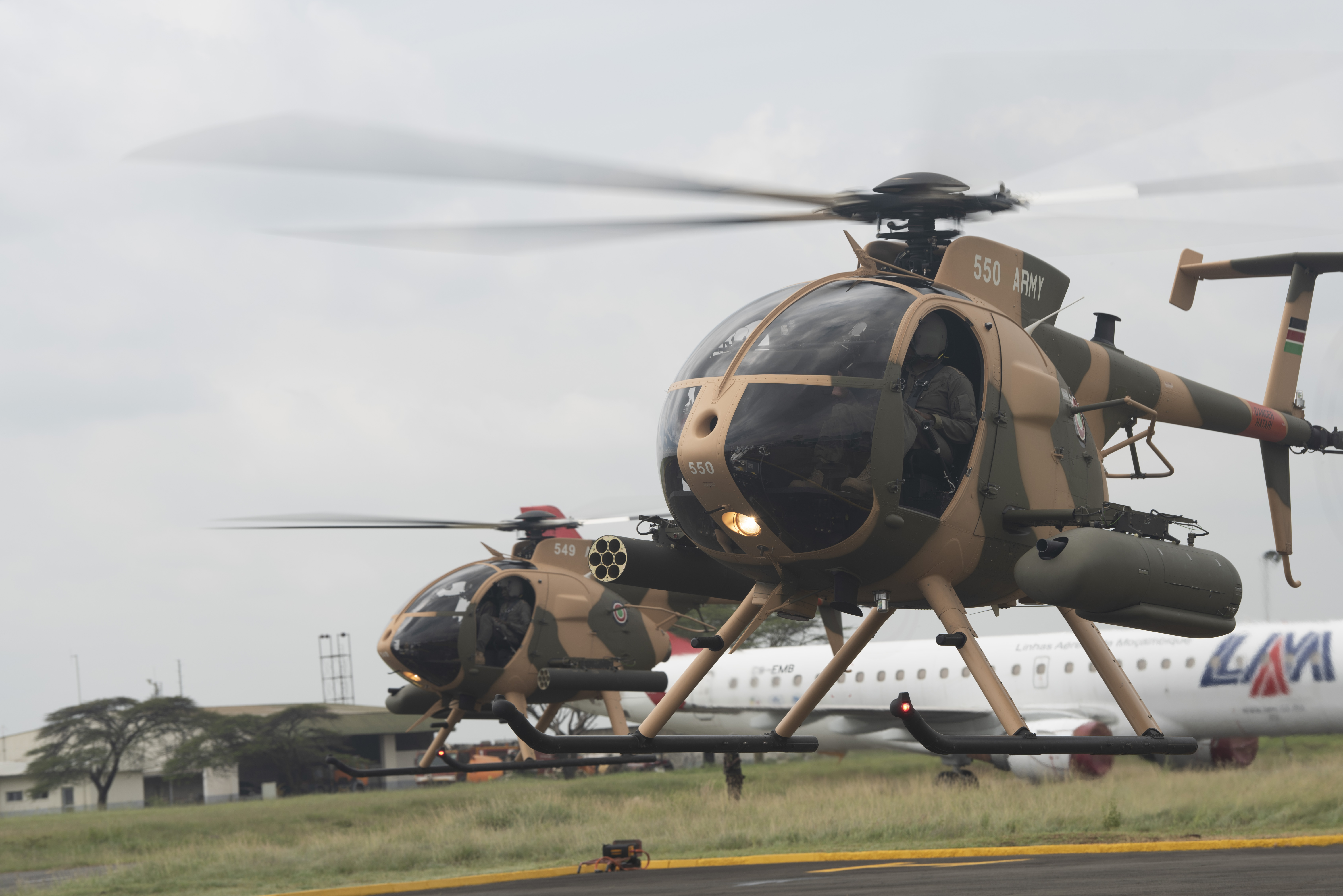 Two MD-530F Cayuse Warrior Helicopters prepare to takeoff during a Helicopter Handover Ceremony at Embakasi Barracks, Kenya, Jan. 23, 2020. The ceremony (During the ceremony, six MD-530F Cayuse Warrior helicopters were delivered to the KDF in a symbolic handover. Six more MD-530F helicopters will be delivered to the KDF in the near future. (U.S. Air Force photo by Tech. Sgt. Ashley Nicole Taylor)