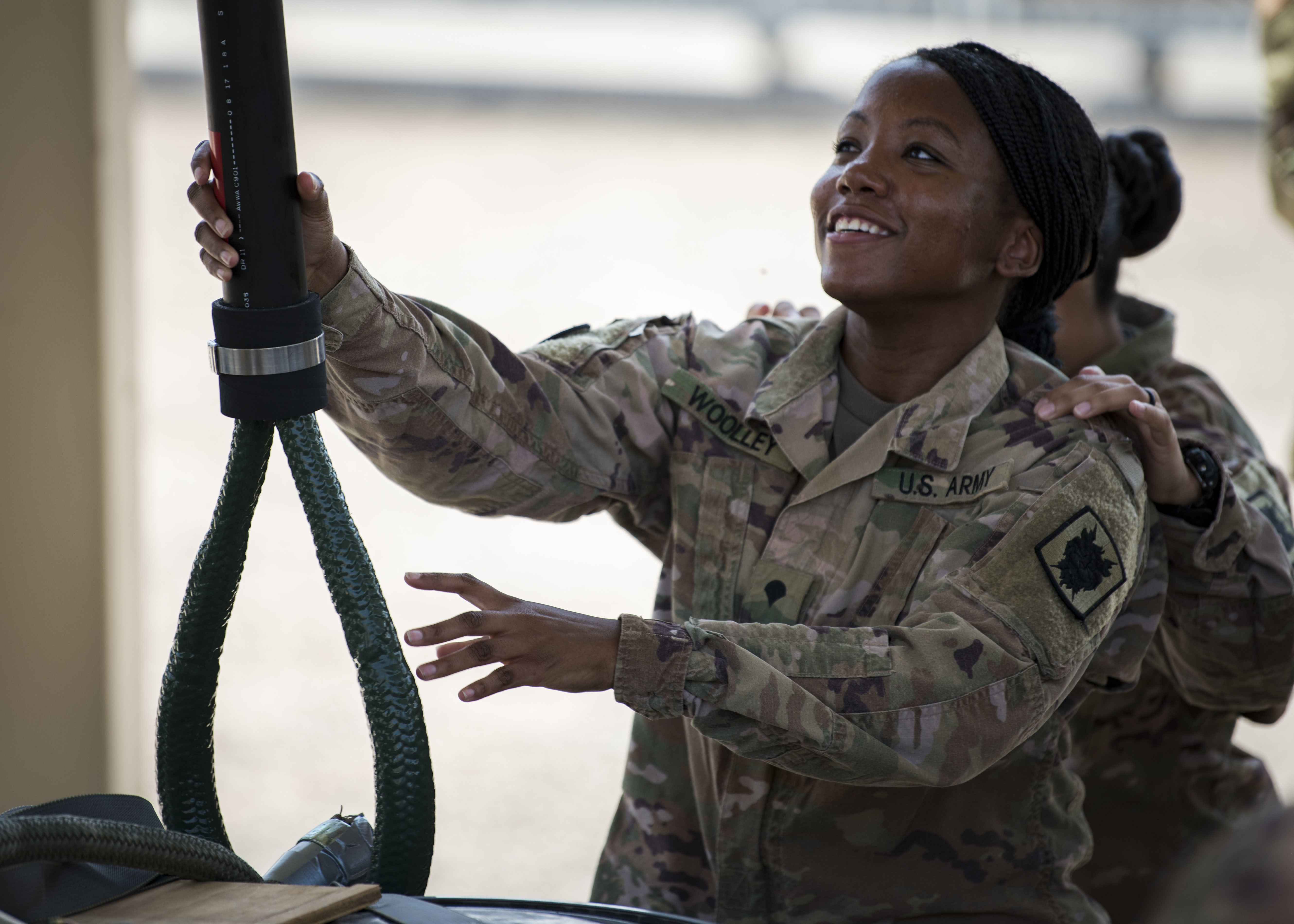 U.S. Army Spc. April Woolley, help desk technician, Communications Directorate, Combined Joint Task Force – Horn of Africa (CJTF-HOA), simulates connecting palletized materials to a helicopter during a sling load training class at Camp Lemonnier, Djibouti, Feb. 27, 2020. The class was designed to familiarize service members with basic sling load procedures, capabilities and operations. (U.S. Air Force photo by Senior Airman Dylan Murakami)