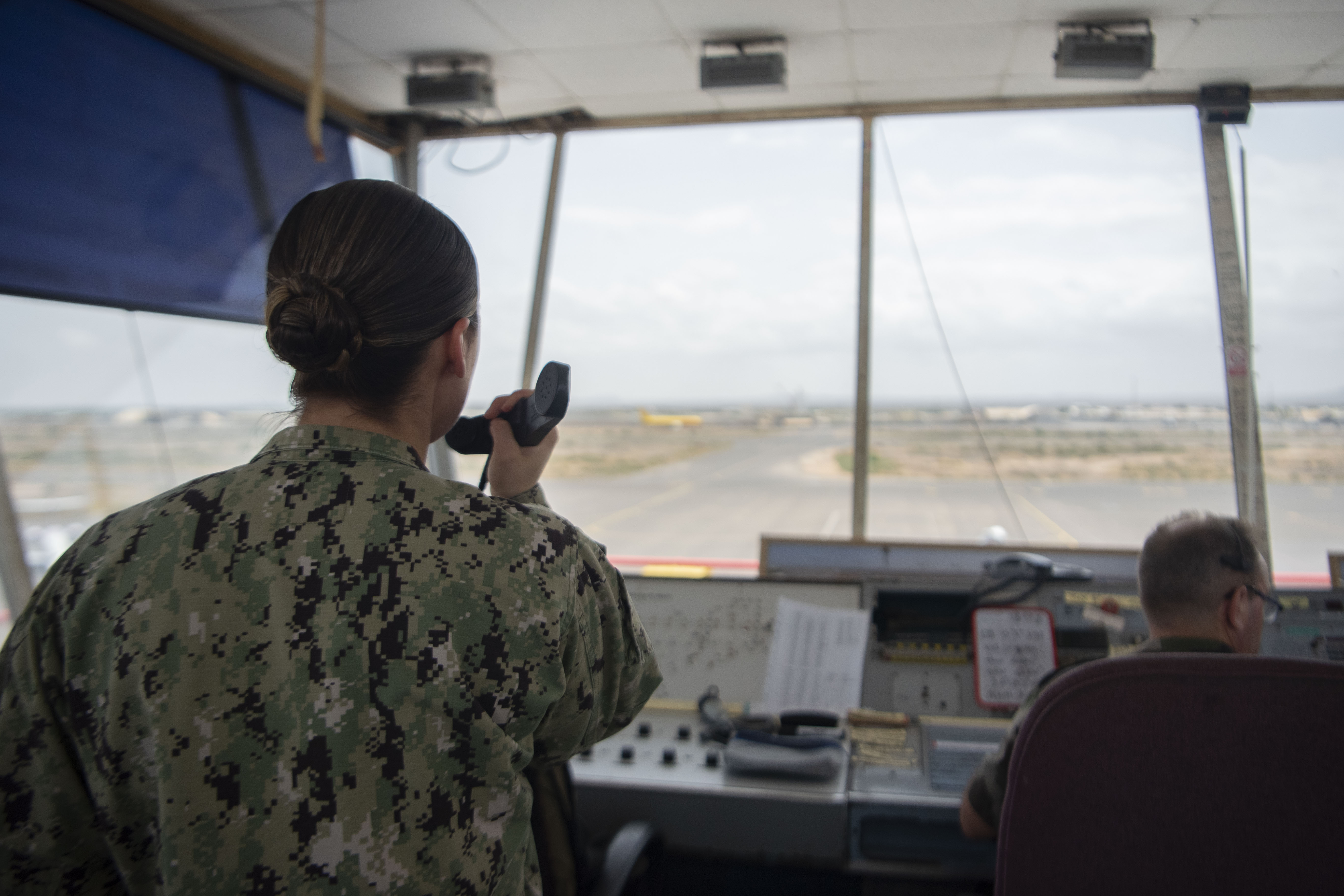 U.S. Navy Air Traffic Controller 1st Class Kristy Lescrynski, Combined Joint Task Force-Horn of Africa (CJTF-HOA), air traffic control training chief, left, directs an aircraft into takeoff position at Djibouti-Ambouli International Airport, March 17, 2020. Prior to the implementation of U.S. Centers for Disease Control and Prevention safety guidelines, Lescrynski worked in Ambouli's tower to coordinate with host nation and coalition partners to ensure smooth air and ground operations at the airport. Since social distancing was implemented, U.S. controllers work out of a watch tower elsewhere on the flight line and maintain contact with Ambouli using alternate communication methods. (U.S. Air Force photo by Senior Airman Gage Daniel)